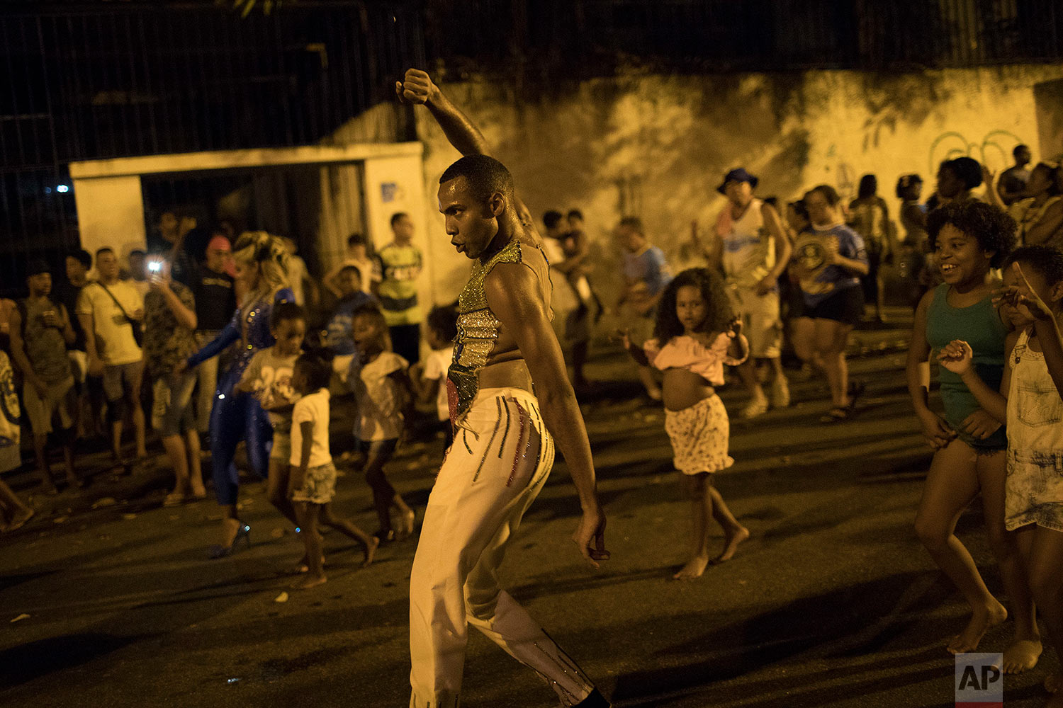"""In this Jan. 22, 2018 photo, a member of the Paraiso do Tuiuti samba school rehearses his group's dances and songs, which this year make reference to Brazil's history with slavery, as residents follow in Rio de Janeiro, Brazil. """"My god, my god, has slavery been extinguished?"""" go the lyrics in Portuguese. (AP Photo/Leo Correa)"""
