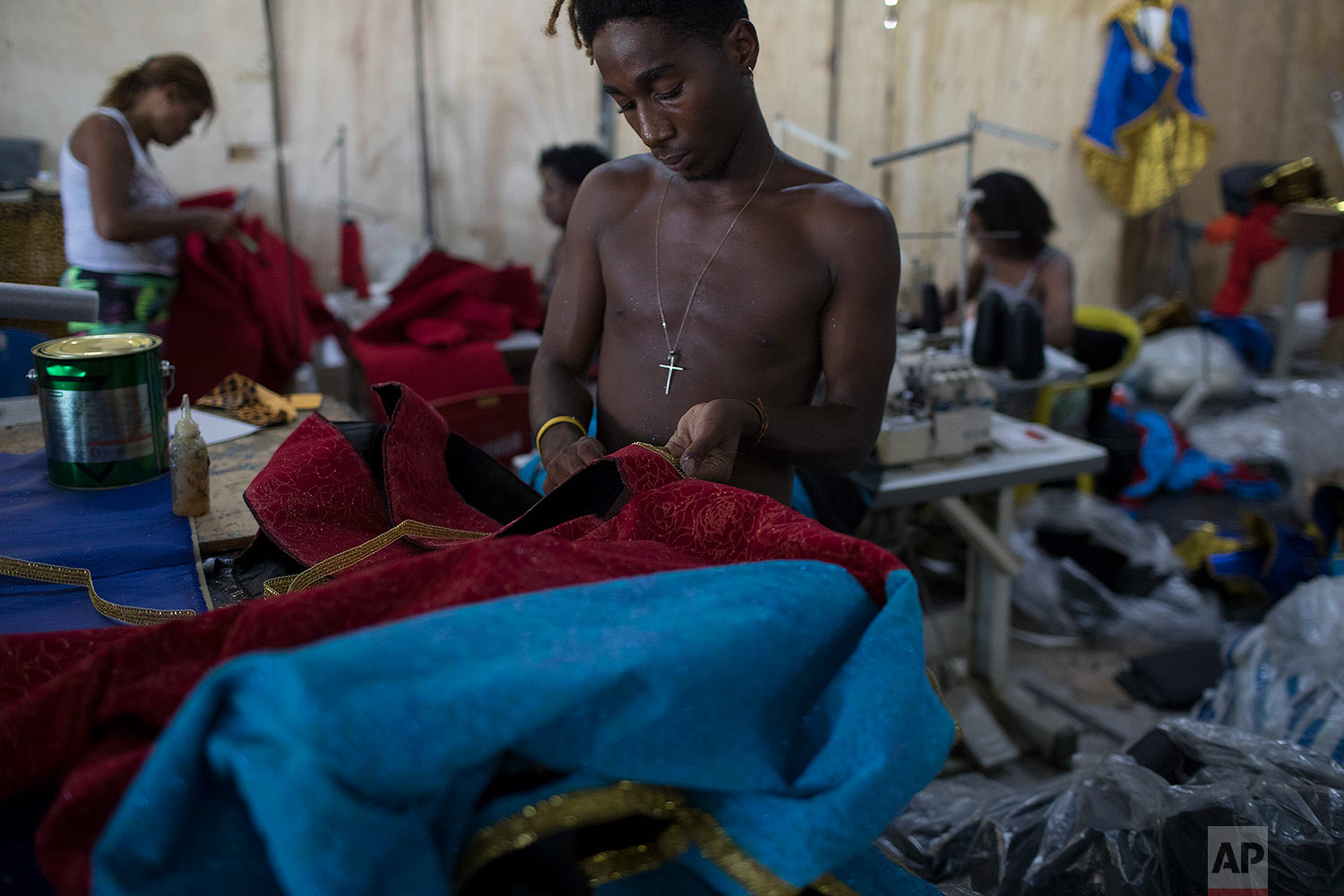In this Jan. 16, 2018 photo, a man creates a carnival costume at the Paraiso do Tuiuti samba school, whose carnival theme this year is Brazil's history with slavery, in Rio de Janeiro, Brazil. Besides Brazil's inequalities in wealth distribution, the group complains about last year's labor law changes that scaled back benefits and made it easier for employers to hire temporary workers. (AP Photo/Leo Correa)