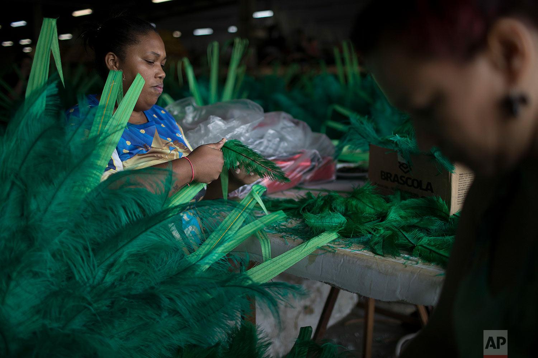 In this Jan. 16, 2018 photo, Josiane de Almeida works with feathers to create carnival costumes for the Paraiso do Tuiuti samba school, whose theme this year is Brazil's history with slavery, in Rio de Janeiro, Brazil. (AP Photo/Leo Correa)