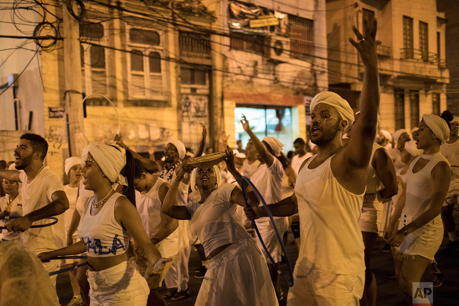 """In this Jan. 22, 2018 photo, members of the Paraiso do Tuiuti samba school rehearse their dances and songs that make reference to Brazil's history with slavery, in the streets of Rio de Janeiro, Brazil. """"It's not just racism against blacks or whites,"""" said Dandara Silva, a hairdresser and dancer in the group. """"There is a form of social slavery and we are fighting against that."""" (AP Photo/Leo Correa)"""