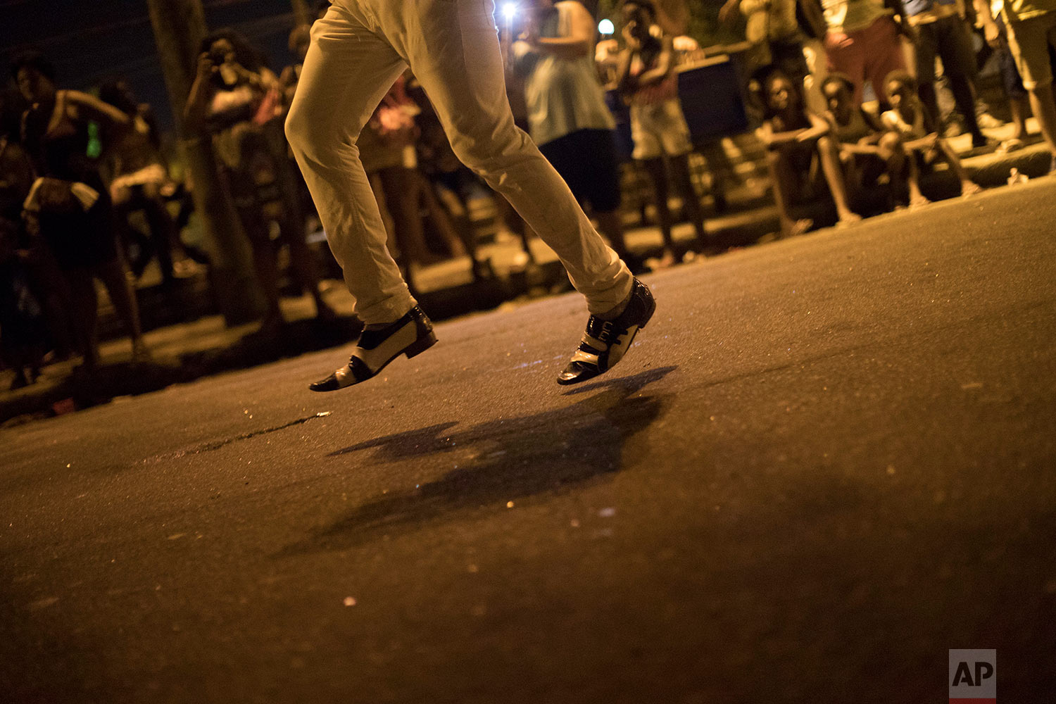 In this Jan. 22, 2018 photo, a member of the Paraiso do Tuiuti samba school rehearses the school's dances and songs, which this year make reference to Brazil's history with slavery, in the streets of Rio de Janeiro, Brazil. In the Sao Cristovao neighborhood, an area where members of the Portuguese royal family used to live, thousands watched as the school rehearsed for its appearance at the Sambadrome on Feb. 11. (AP Photo/Leo Correa)
