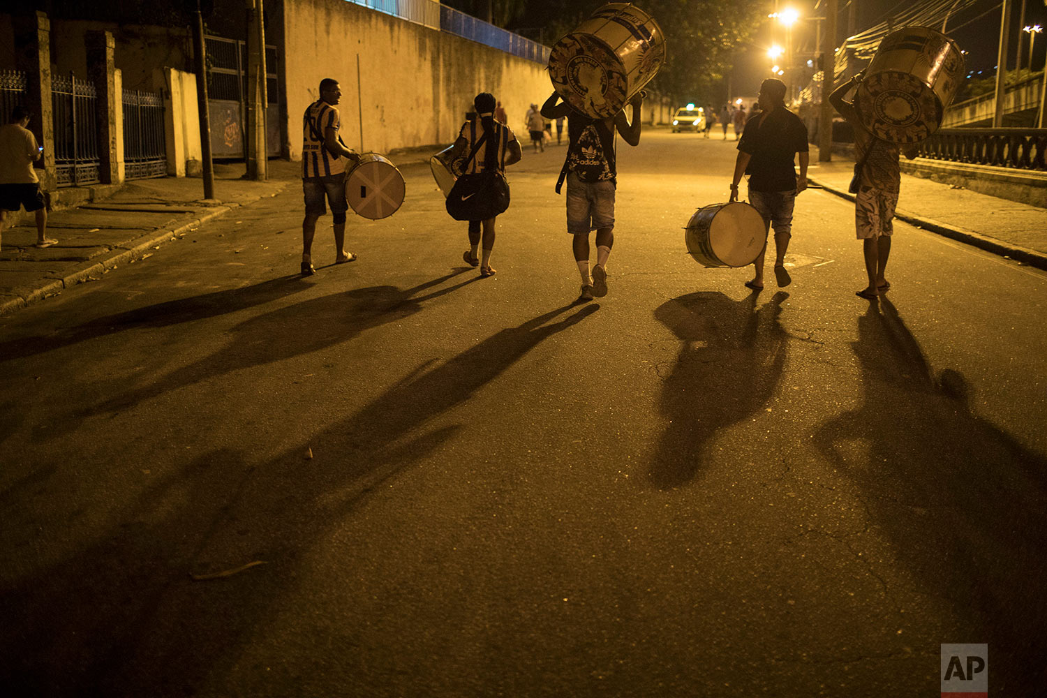 """In this Jan. 22, 2018 photo, drummers from the Paraiso do Tuiuti samba school walk to a street rehearsal of their dances and songs, which this year make reference to Brazil's history with slavery, in Rio de Janeiro, Brazil. """"Our music questions whether slavery is actually over,"""" said Jack Vasconcelos, the group's art director. (AP Photo/Leo Correa)"""