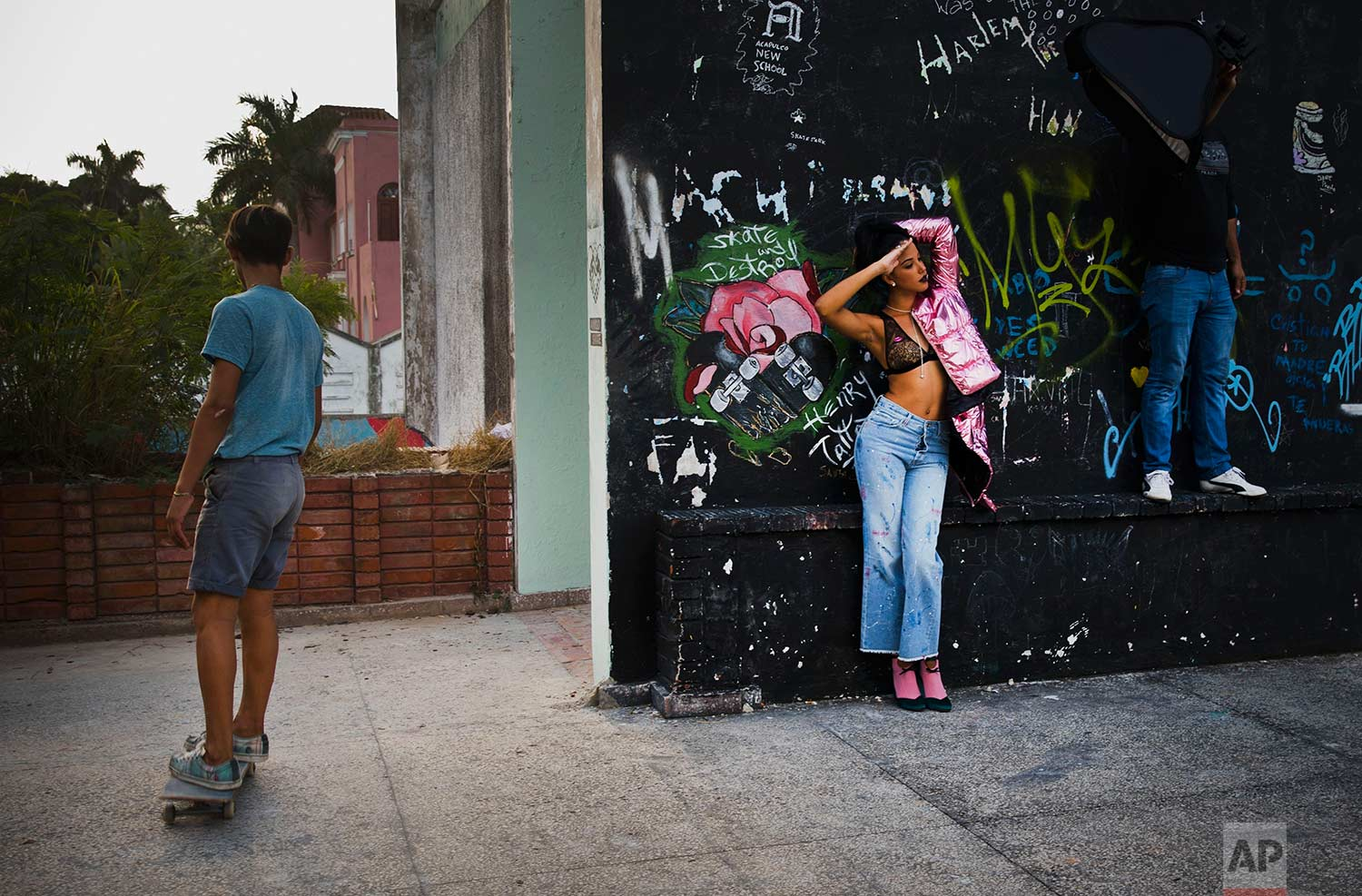 In this Jan. 11, 2018 photo, a young model and a member of the lighting crew use as their backdrop an abandoned gym that was converted into space for skateboarders, the day of the space's inauguration inside the Educational complex Ciudad Libertad, a former military barracks that the late Fidel Castro turned into a school complex after the revolution in Havana, Cuba. (AP Photo/Ramon Espinosa)