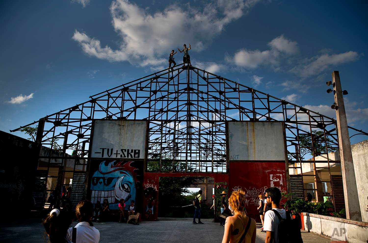 In this Jan. 11, 2018 photo, people arrive to an abandoned gym recently converted into a space for skateboarders, the day of its inauguration inside the Educational complex Ciudad Libertad, a former military barracks that the late Fidel Castro turned into a school complex after the revolution in Havana, Cuba. (AP Photo/Ramon Espinosa)