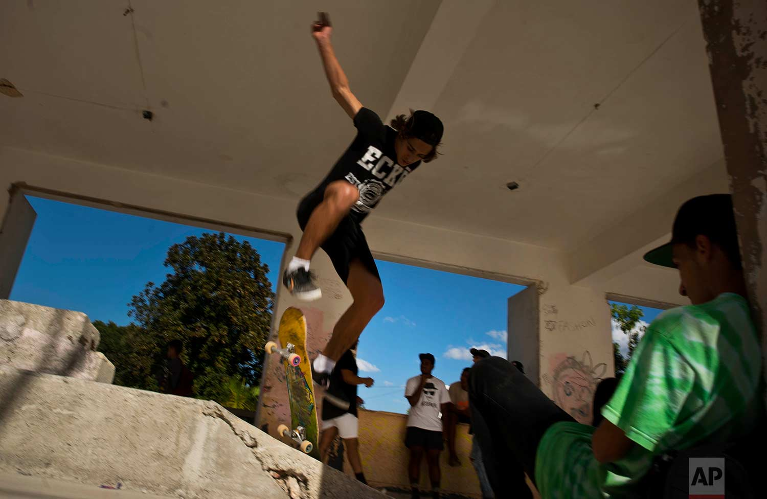 In this Jan. 11, 2018 photo, a skater jumps during the inauguration of a new recreational space for skateboarders, created in an abandoned gym at the Educational complex Ciudad Libertad, a former military barracks that the late Fidel Castro turned into a school complex after the revolution in Havana, Cuba. (AP Photo/Ramon Espinosa)