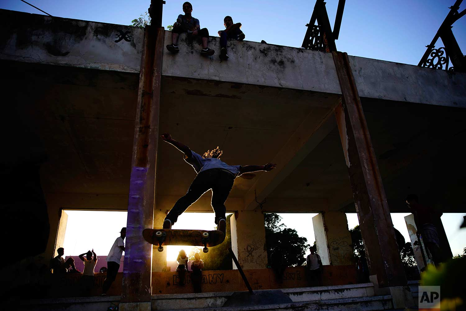 In this Jan. 11, 2018 photo, a skater jumps a ramp during the inauguration of a new recreational space for skateboarders, created in an abandoned gym at the Educational complex Ciudad Libertad, a former military barracks that the late Fidel Castro turned into a school complex after the revolution in Havana, Cuba. (AP Photo/Ramon Espinosa)