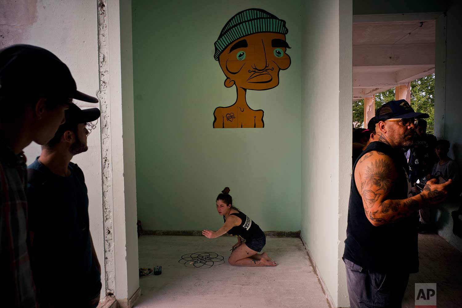 In this Jan. 11, 2018 photo, an artist decorates the floor with a mural during the inauguration of a new recreational space for skateboarders, created in an abandoned gym at the Educational complex Ciudad Libertad, a former military barracks that the late Fidel Castro turned into a school complex after the revolution in Havana, Cuba. (AP Photo/Ramon Espinosa)