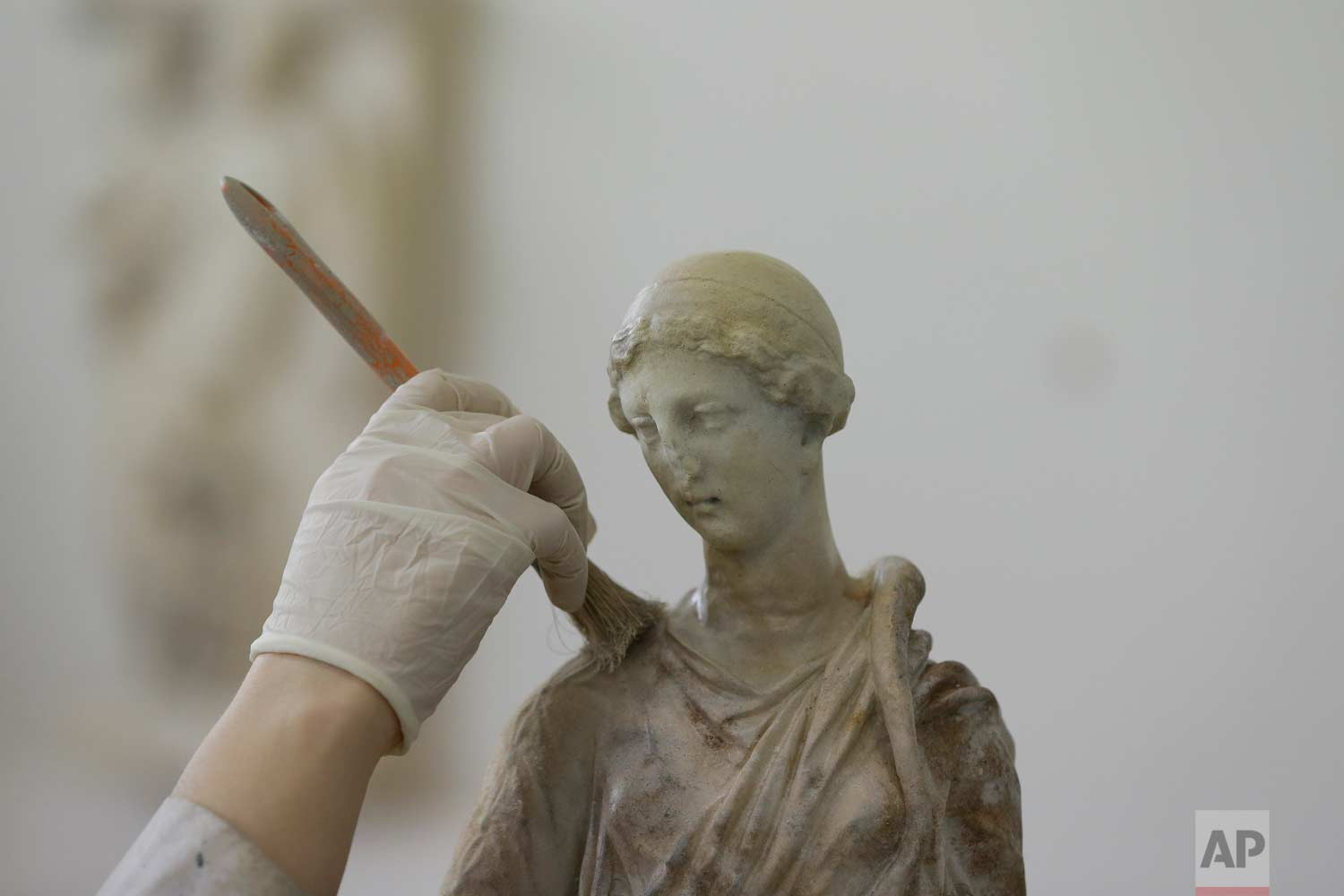 In this Monday, Jan. 22, 2018, an employee of Culture Ministry paints a plaster replica of a statue at the Lab in Athens. A team of about 50 fine arts graduates work on a range of sculptures, from a three-inch hare from Roman-era Macedonia to a seven-foot statue of Zeus, or Poseidon, made in the mid-5th century B.C. and one of the star exhibits of the National Archaeological Museum in Athens. (AP Photo/Thanassis Stavrakis)