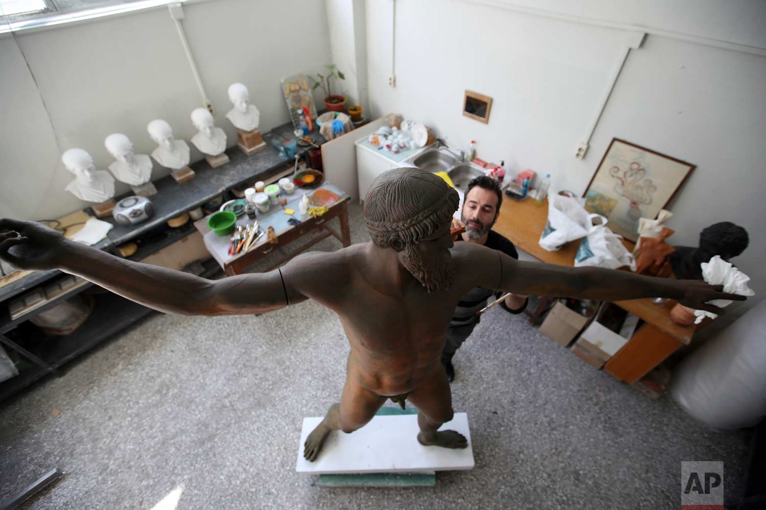 In this Monday, Jan. 22, 2018, a sculptor paints a plaster replica of the seven-foot bronze statue of Zeus, or Poseidon, made in the mid-5th century B.C. in the Culture Ministry's Lab in Athens. (AP Photo/Thanassis Stavrakis)