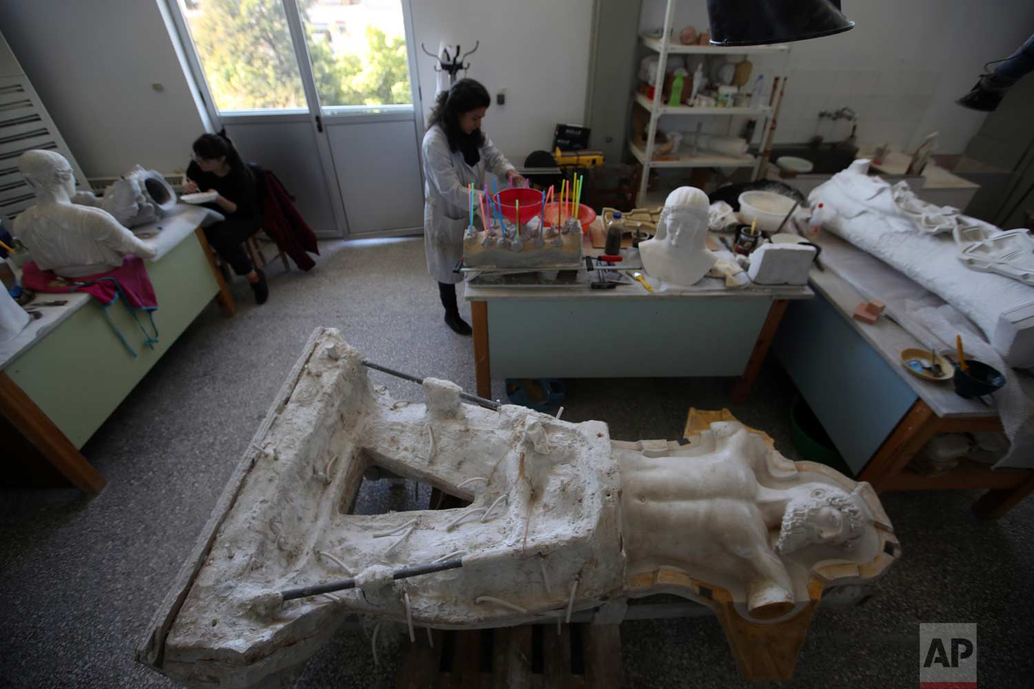 In this Tuesday, Jan. 16, 2018, sculptors work in the Culture Ministry's Lab in Athens. (AP Photo/Thanassis Stavrakis)
