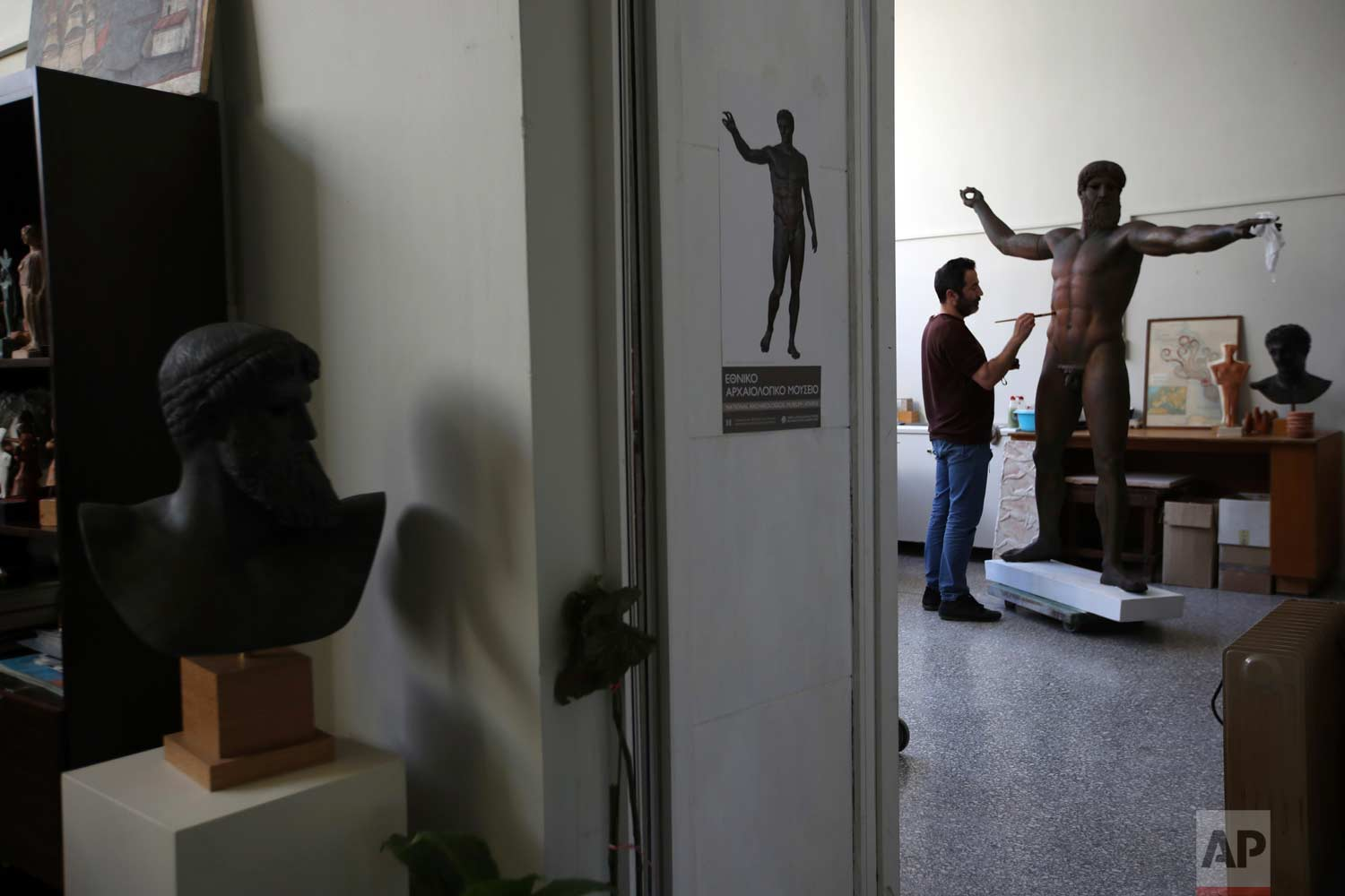 In this Tuesday, Jan. 16, 2018, a sculptor paints a plaster replica of the seven-foot bronze statue of Zeus, or Poseidon, made in the mid-5th century B.C. in the Culture Ministry's Lab in Athens. (AP Photo/Thanassis Stavrakis)