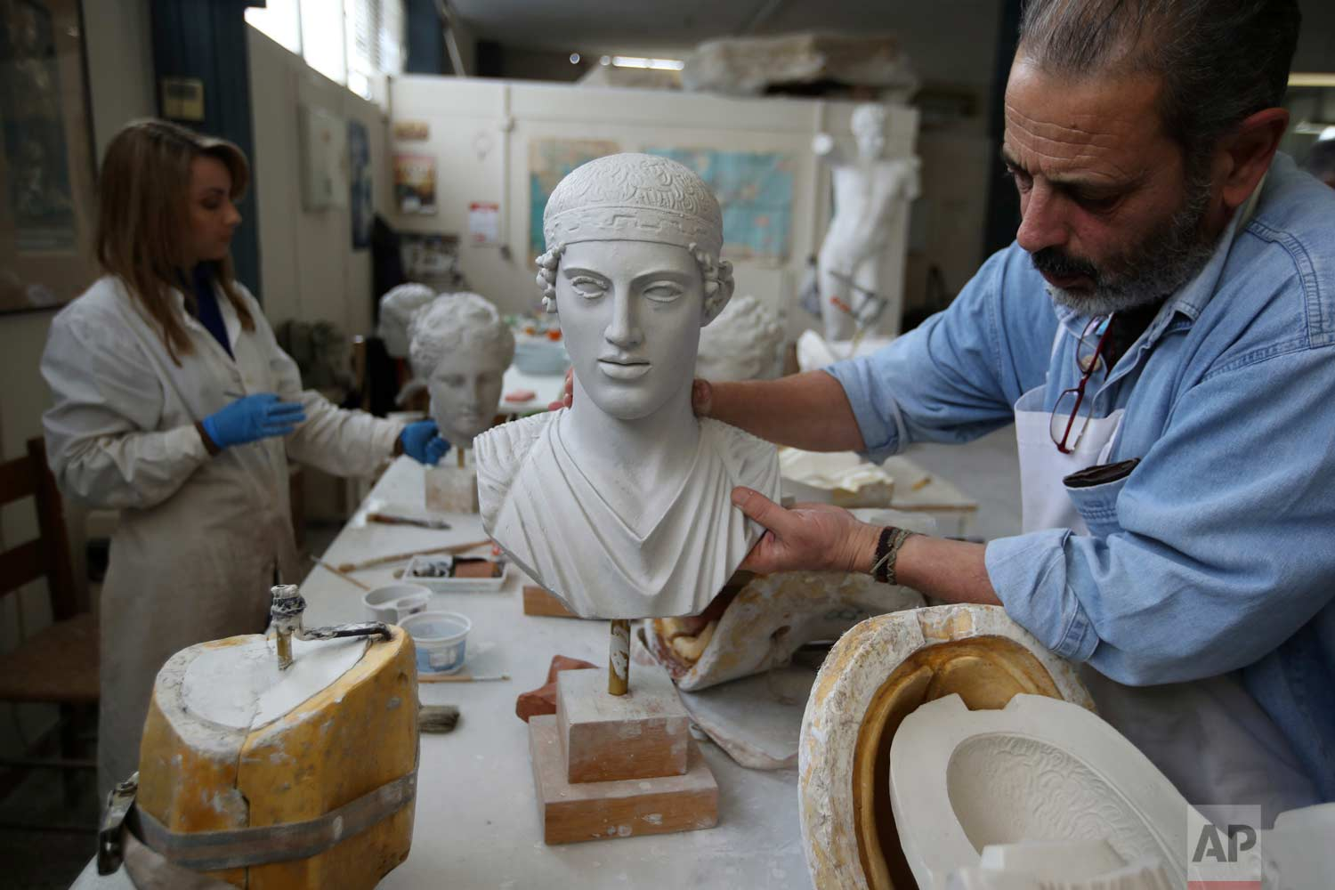 In this Wednesday, Jan. 17, 2018, a worker places a copy of the head of Kouros in Culture Ministry's Lab in Athens. (AP Photo/Thanassis Stavrakis)