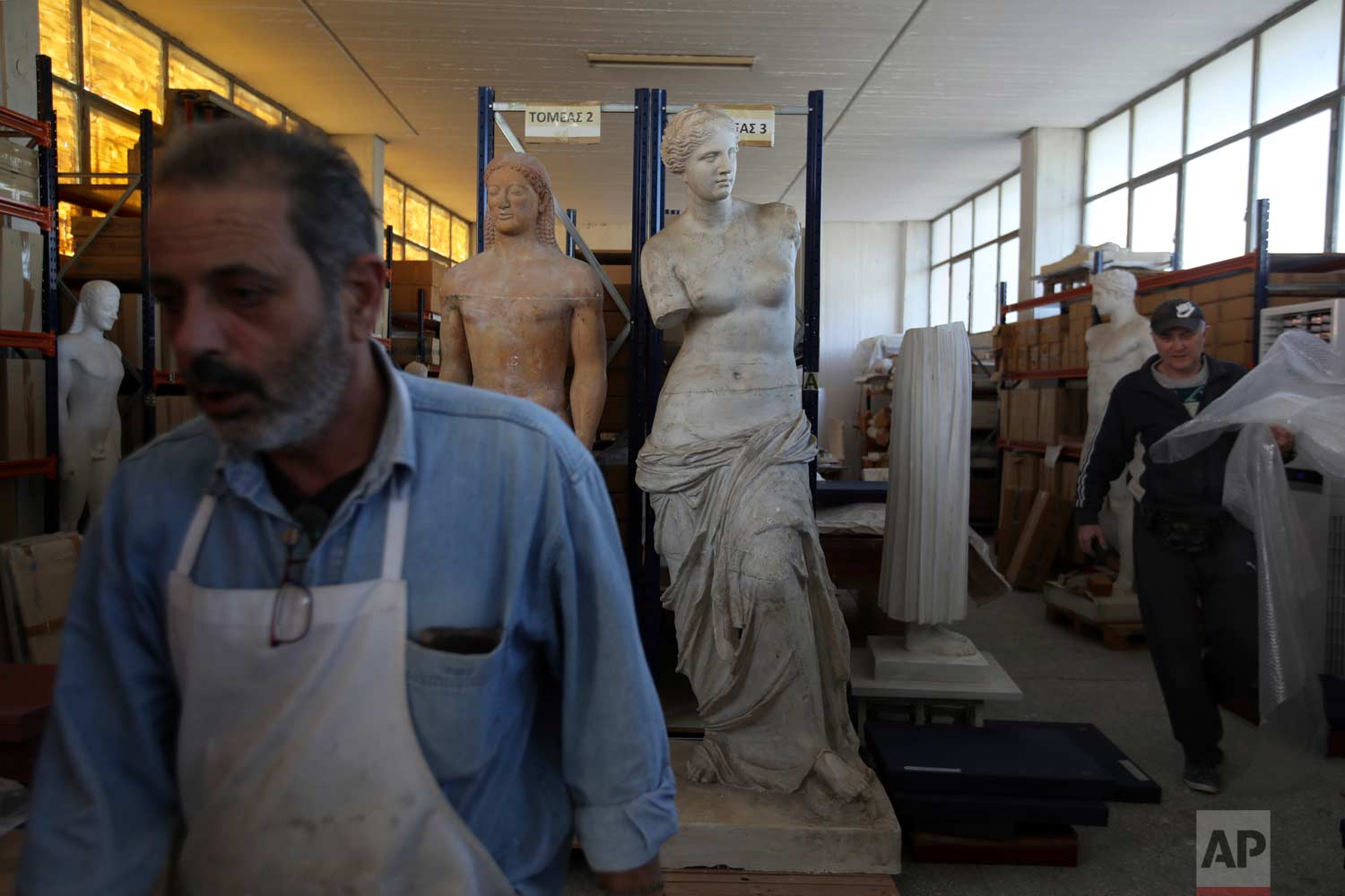 In this Monday, Jan. 22, 2018, employees work at the warehouse of Culture Ministry's Lab where they place the replicas used to make moulds in Athens. (AP Photo/Thanassis Stavrakis)