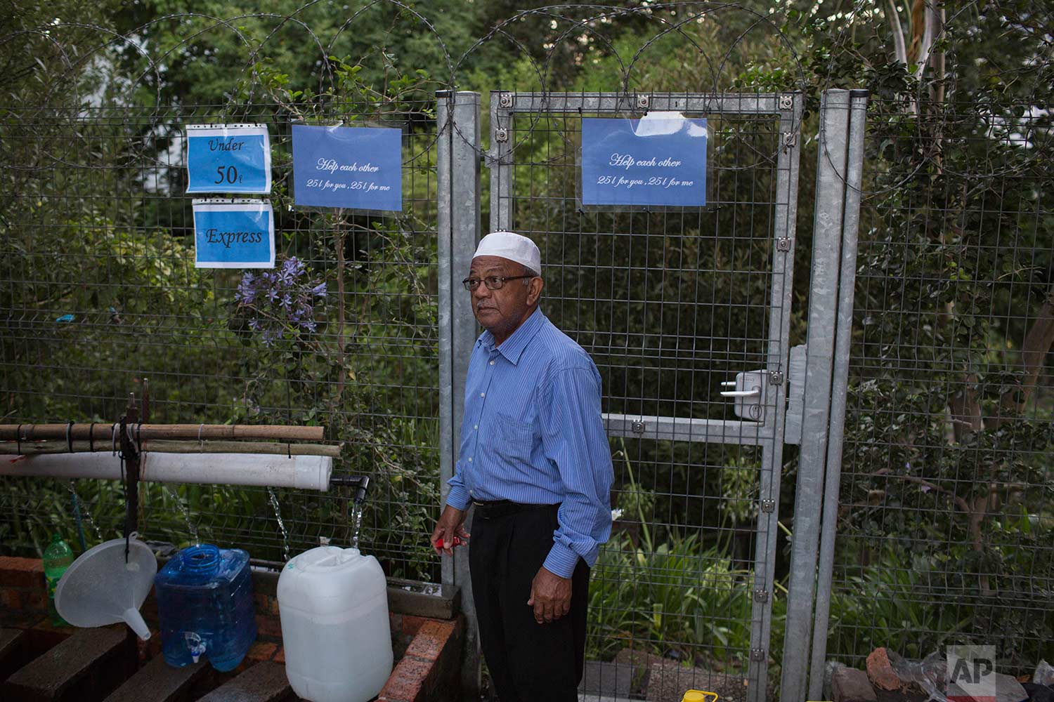 A man collects water from a source of natural spring water in Cape Town, Thursday, Feb. 1, 2018. (AP Photo/Bram Janssen)