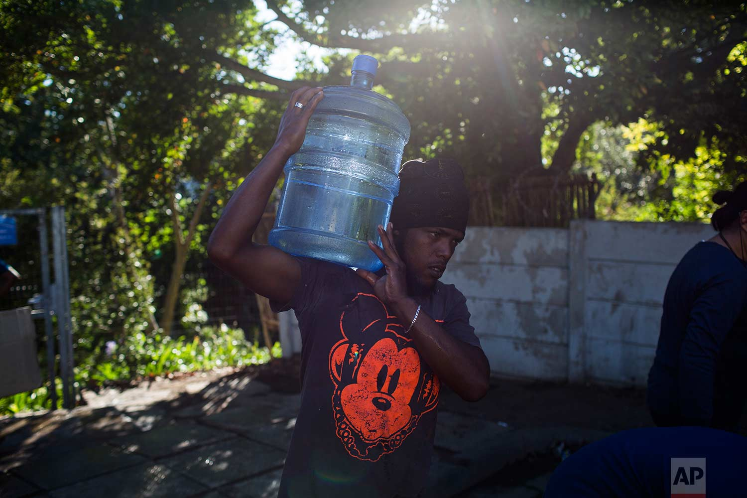 A man carries water at a source for natural spring water in Cape Town, Thursday, Feb. 1, 2018. (AP Photo/Bram Janssen)
