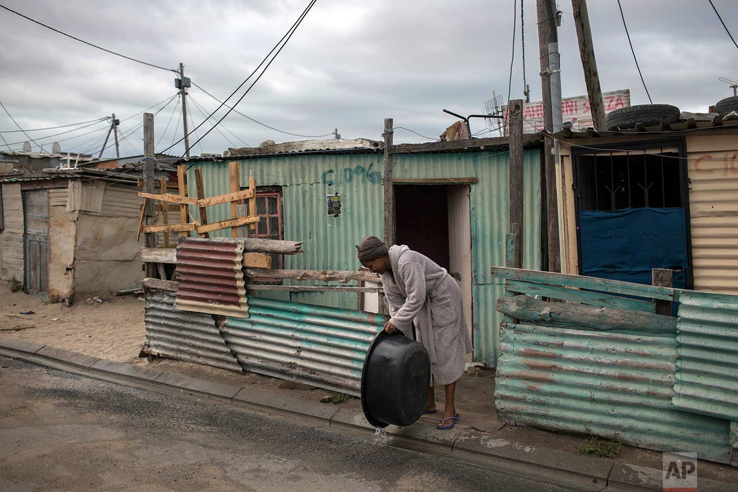 A woman throws away used water in a settlement near Cape Town on Friday, Feb. 2, 2018. (AP Photo/Bram Janssen)