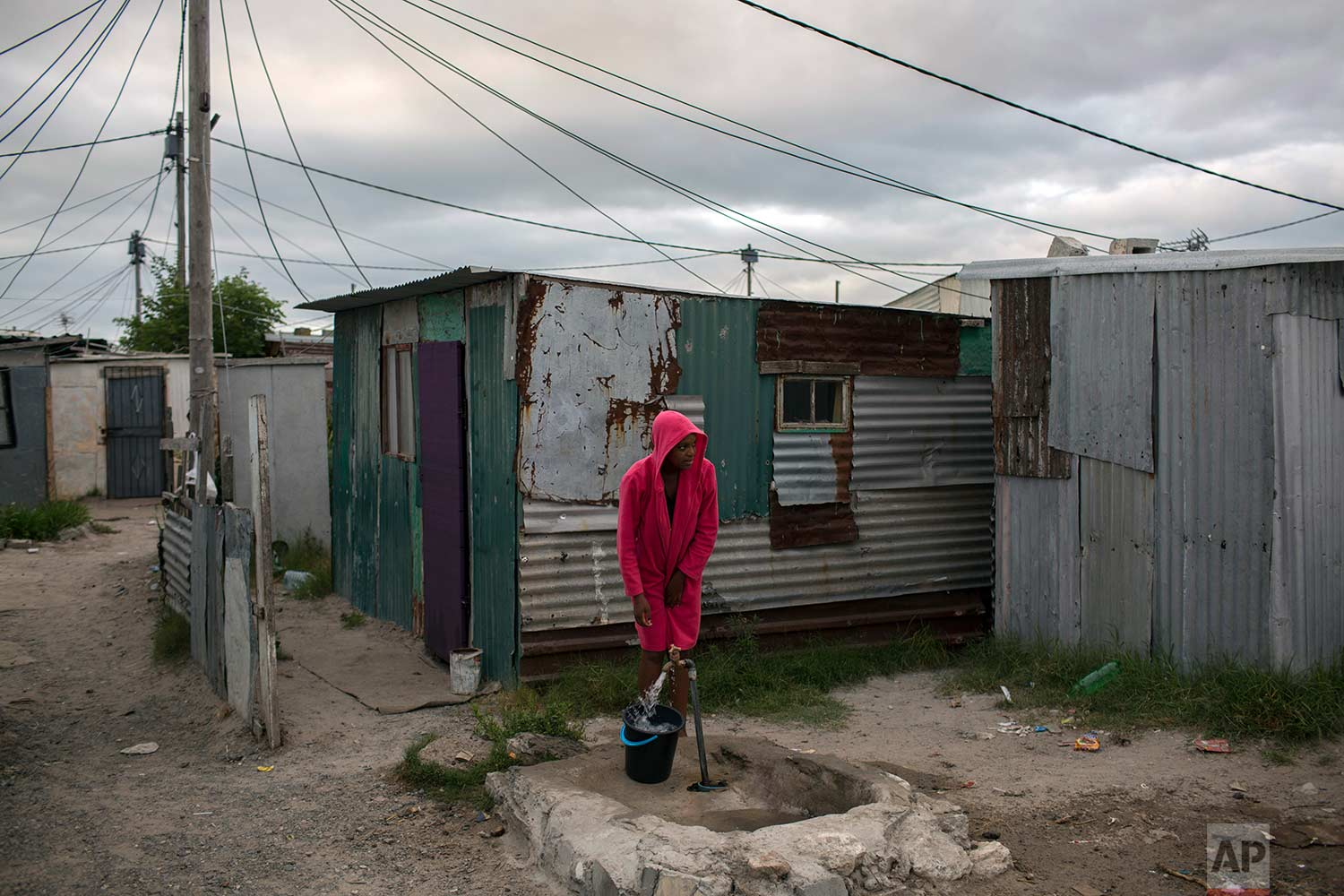 A woman collects water in a settlement near Cape Town on Friday, Feb. 2, 2018. (AP Photo/Bram Janssen)