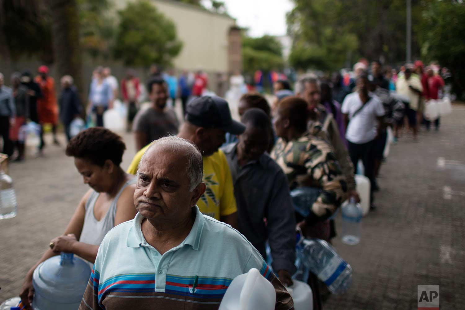 Residents queue to fill containers with water from a source of natural spring water in Cape Town, South Africa, Friday, Feb. 2, 2018. (AP Photo/Bram Janssen)