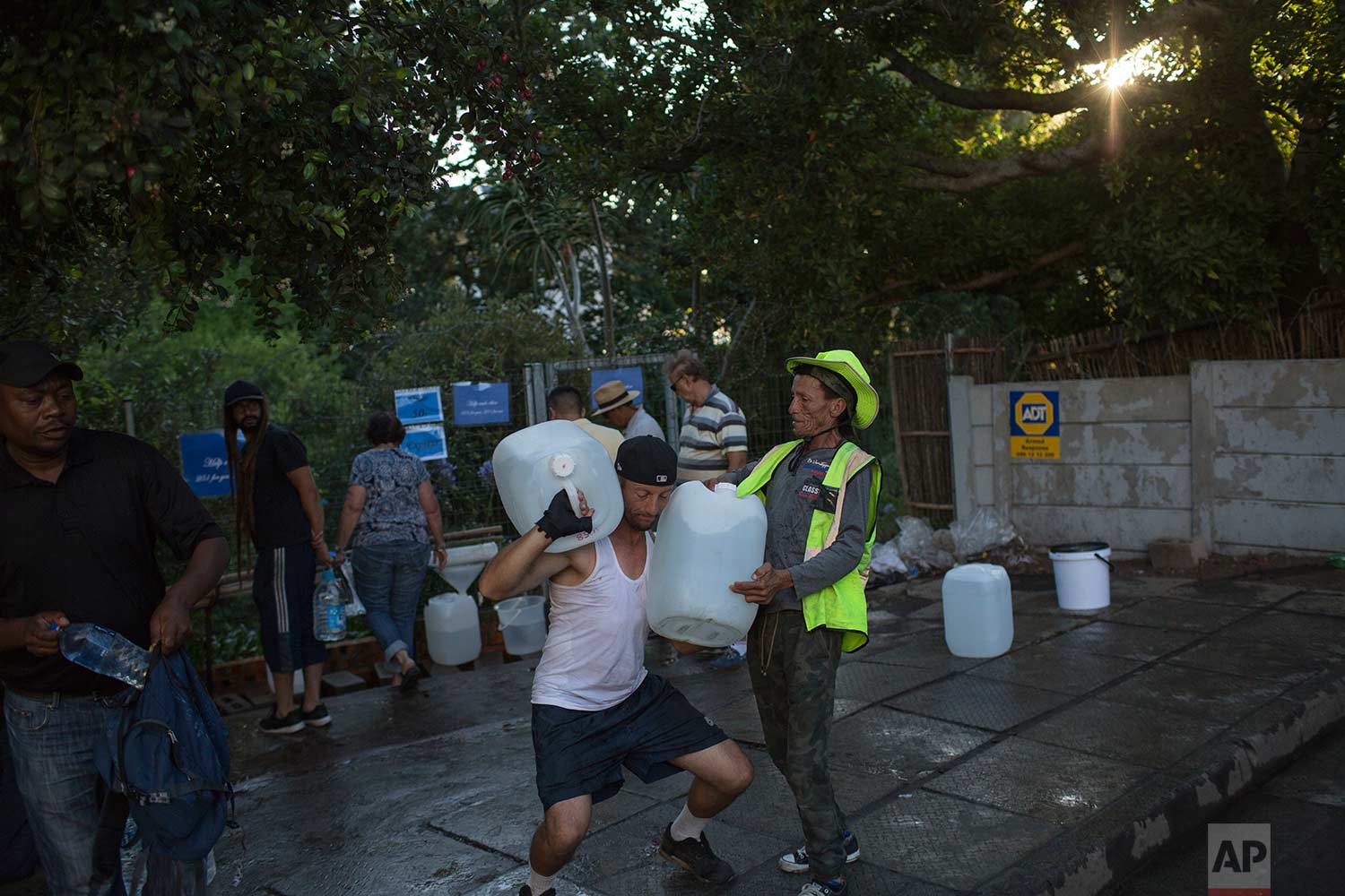 In this Thursday, Feb. 1, 2018 photo, two men help each other carry water at a source for natural spring water in Cape Town. (AP Photo/Bram Janssen)