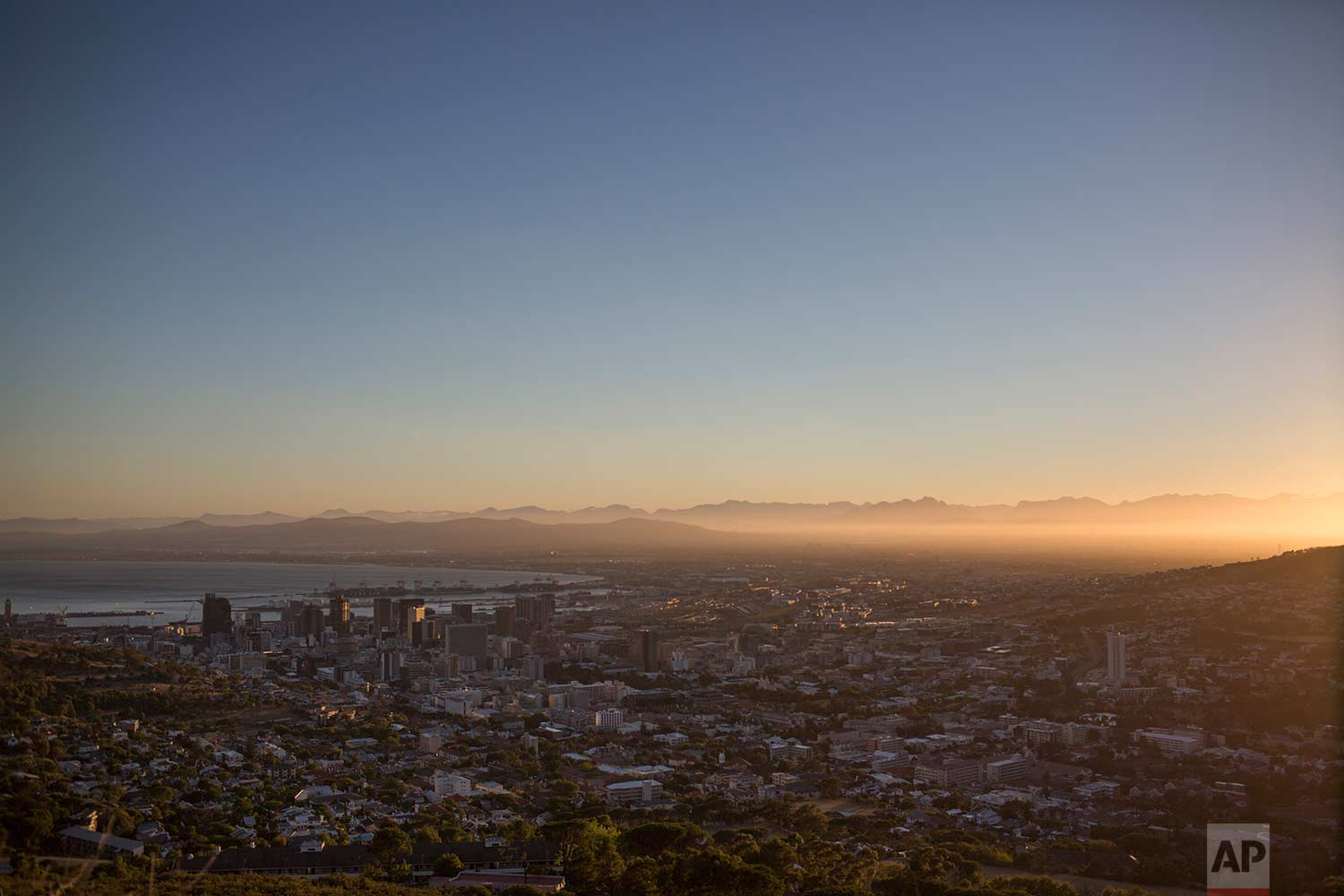In this Saturday, Feb. 3, 2018, the city of Cape Town in South Africa is seen from a hilltop at sunrise. (AP Photo/Bram Janssen)