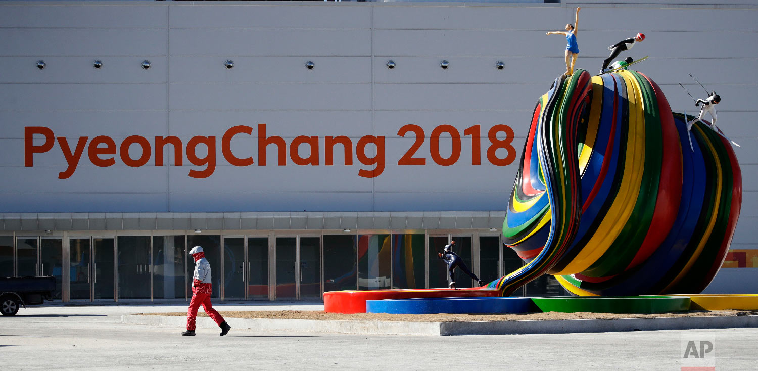 A volunteer passes a piece of artwork at the Pyeongchang Olympic Plaza as preparations continue for the 2018 Winter Olympics in Pyeongchang, South Korea, Monday, Feb. 5, 2018. (AP Photo/Charlie Riedel)