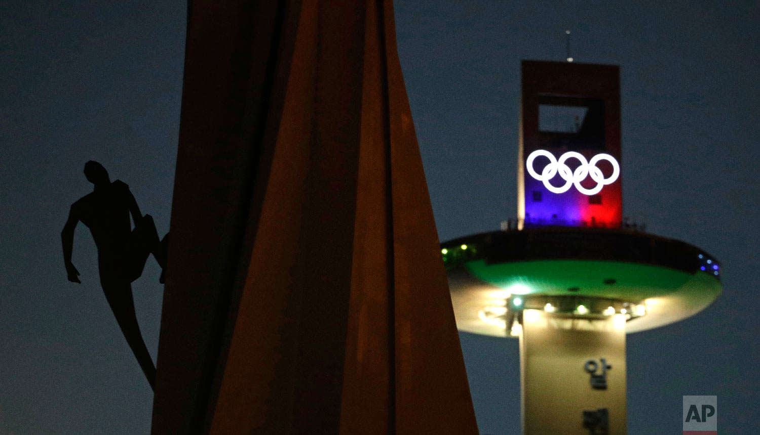 A human figure appears to be climbing an Olympic Cauldron at the Pyeongchang Olympic Plaza as preparations continue for the 2018 Winter Olympics in Pyeongchang, South Korea, Sunday, Feb. 4, 2018. (AP Photo/Charlie Riedel)