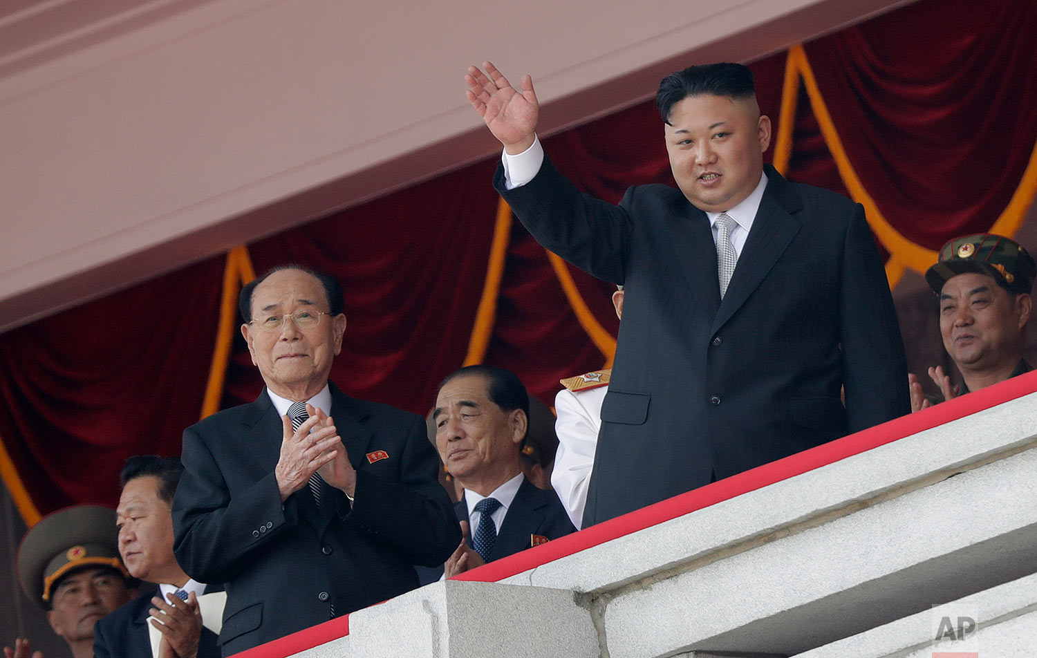 North Korean leader Kim Jong Un, right, waves while Kim Yong Nam, third left, Choe Ryong Hae, second left, and Pak Pong Ju, center, clap during a military parade on Saturday, April 15, 2017, in Pyongyang, North Korea to celebrate the 105th birth anniversary of Kim Il Sung, the country's late founder and grandfather of current ruler Kim Jong Un. (AP Photo/Wong Maye-E)