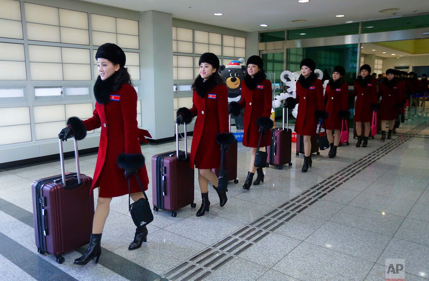 North Korean cheering squads arrive at the Korean-transit office near the Demilitarized Zone in Paju, South Korea, Wednesday, Feb. 7, 2018. A North Korean delegation, including members of a state-trained cheering group, arrived in South Korea on Wednesday for the Pyeongchang Winter Olympics. (AP Photo/Ahn Young-joon. Pool)