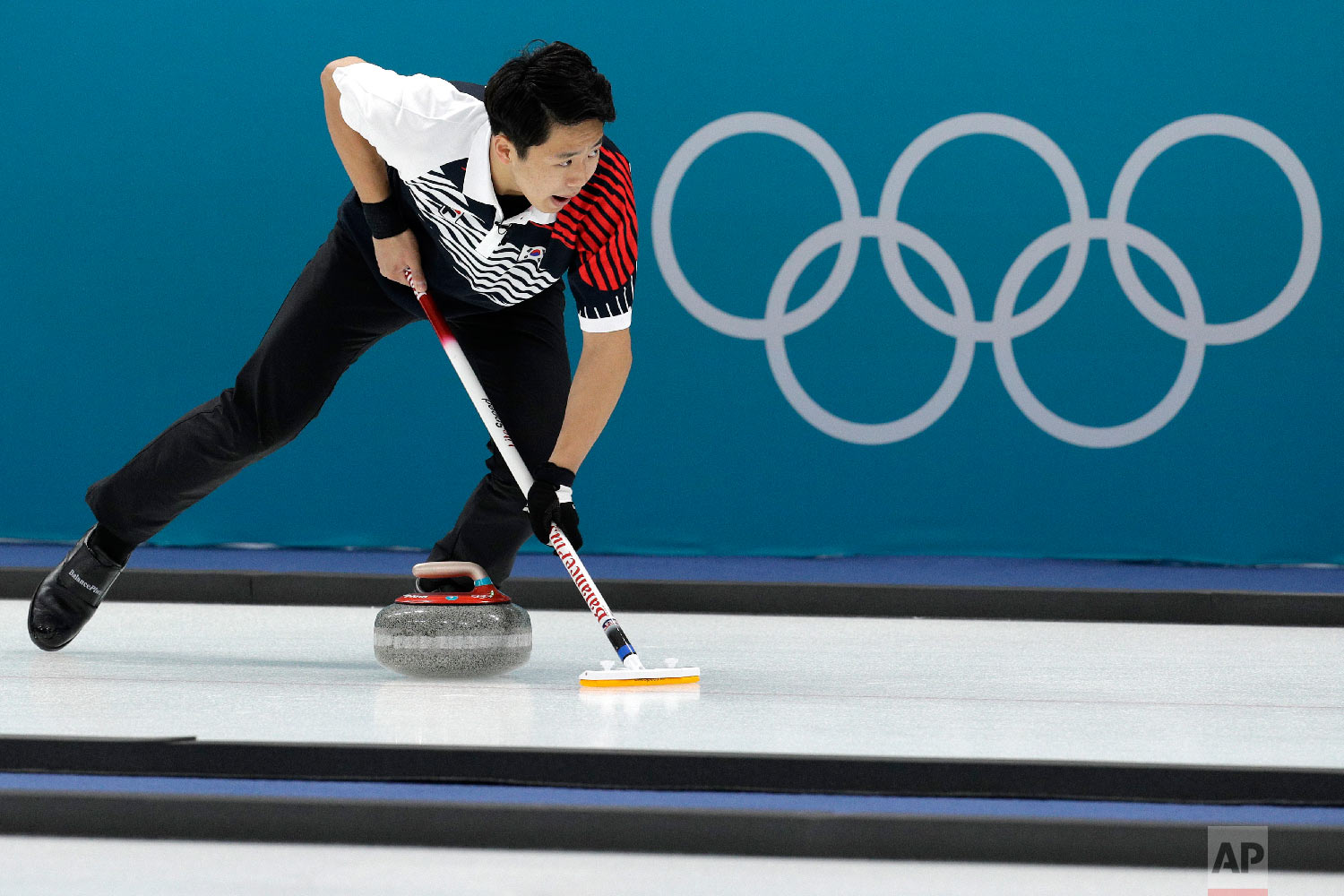 South Korea'sLee Kijeong sweeps ice during their mixed doubles curling match against Olympic Athletes of Russia at the 2018 Winter Olympics in Gangneung, South Korea, Saturday, Feb. 10, 2018. (AP Photo/Aaron Favila)
