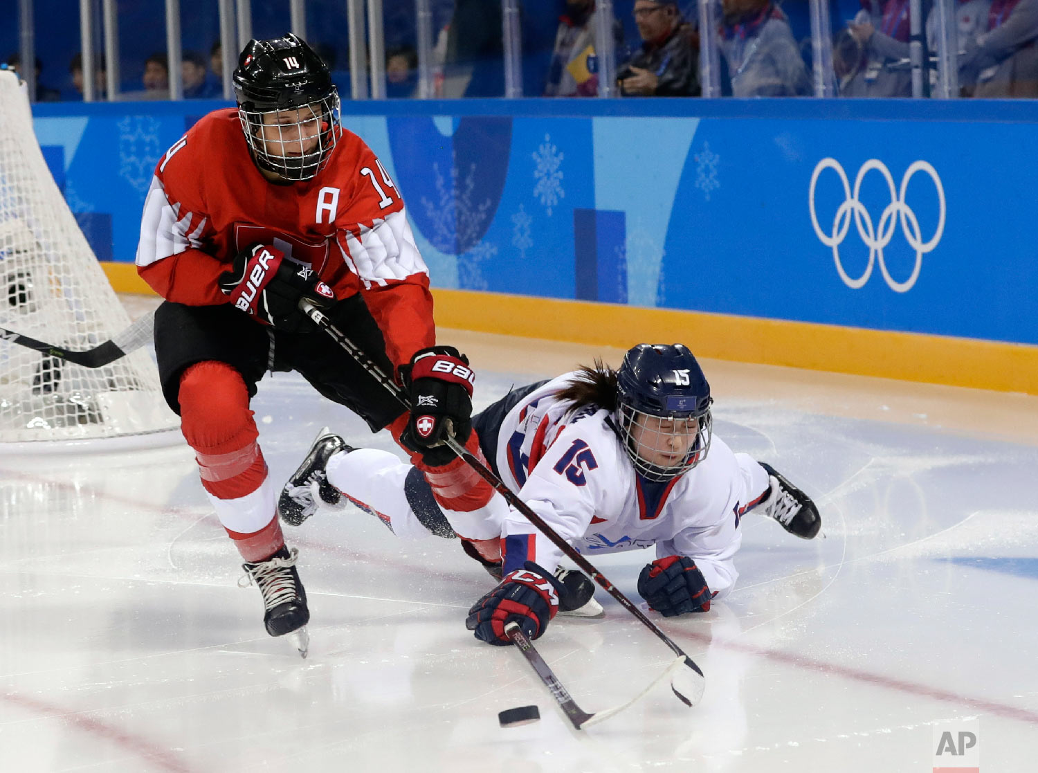 Evelina Raselli (14), of Switzerland, and South Korea's Chaelin Park (15), of the combined Koreas team, battle for the puck during the second period of the preliminary round of the women's hockey game at the 2018 Winter Olympics in Gangneung, South Korea, Saturday, Feb. 10, 2018. (AP Photo/Frank Franklin II)