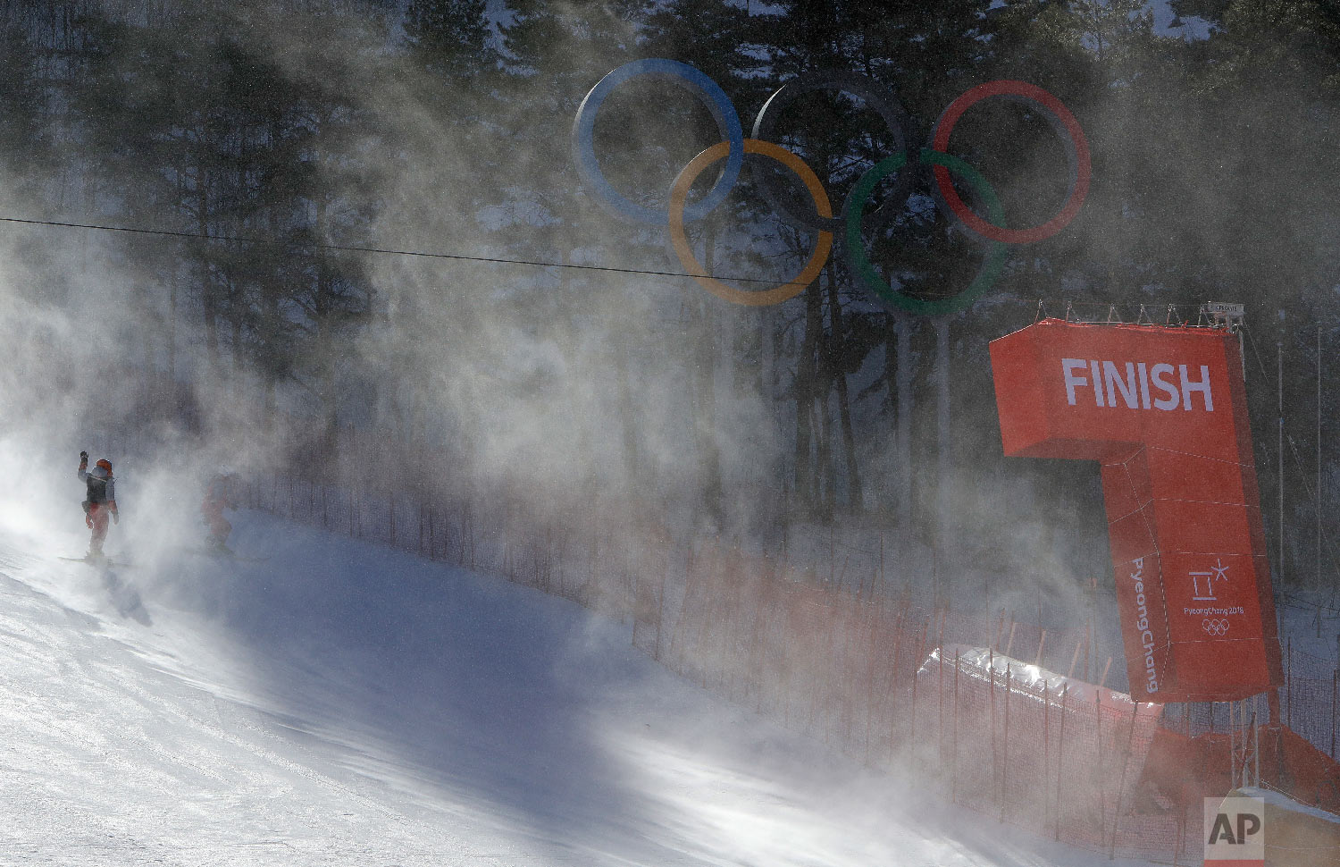 The finish line and Olympic rings shrouded in snow as they carry ski gates after the women's giant slalom was postponed due to high winds at the 2018 Winter Olympics at the Yongpyong Alpine Center, Pyeongchang, South Korea, Monday, Feb. 12, 2018. (AP Photo/Michael Probst)
