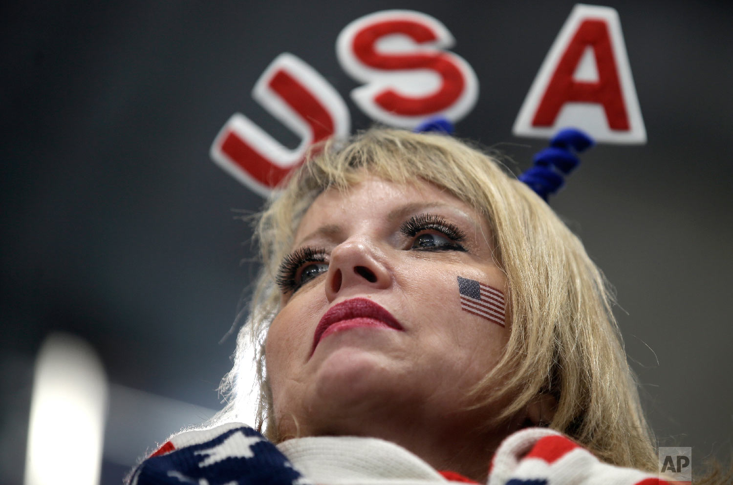 A woman wearing a U.S.A sign on her head watches the mixed doubles curling match at the 2018 Winter Olympics in Gangneung, South Korea, Saturday, Feb. 10, 2018. (AP Photo/Aaron Favila)