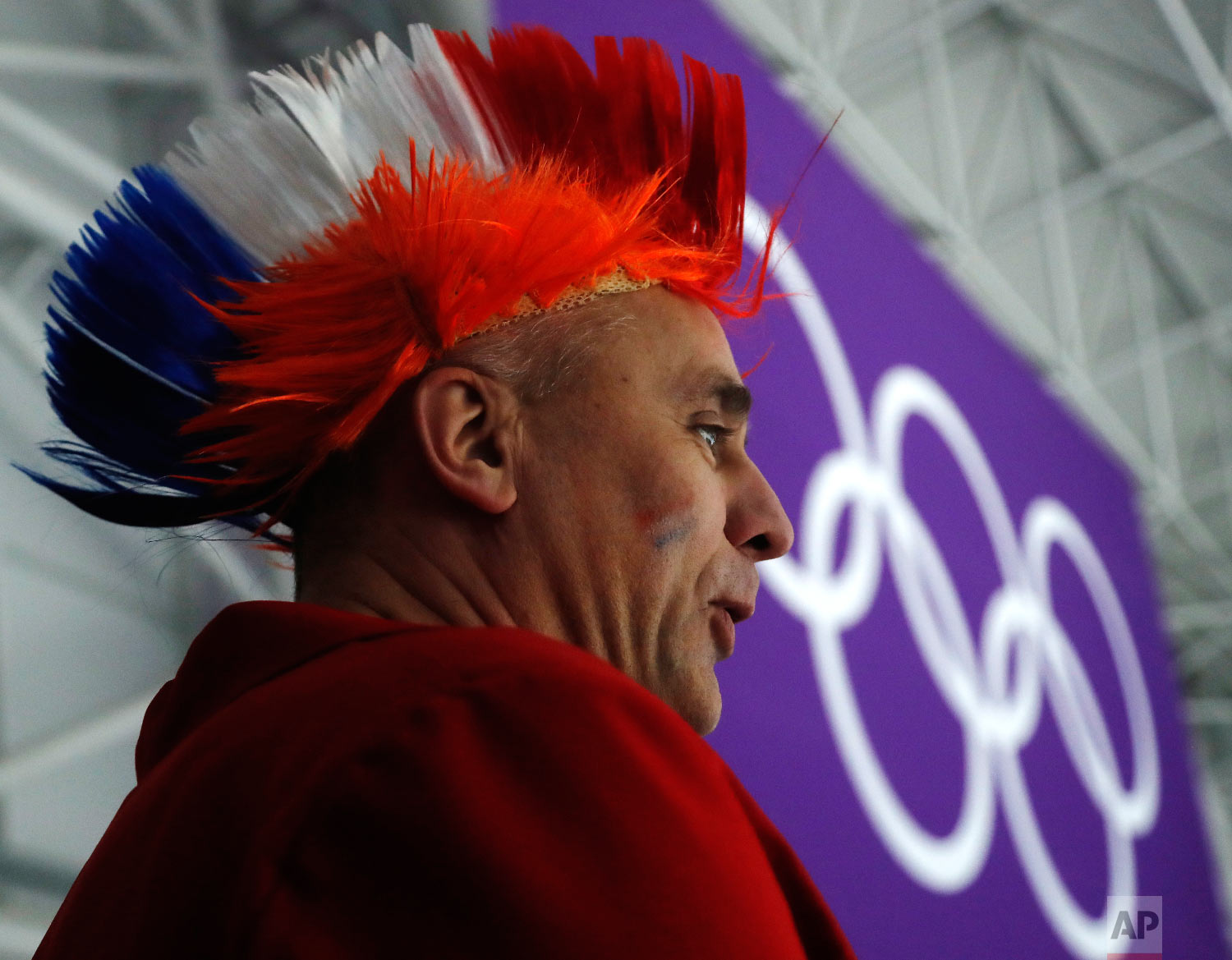 A fan of the Dutch speedsters wears a wig in the colors of the Dutch flag as he waits for the start of the women's 1500 meters speedskating race at the Gangneung Oval at the 2018 Winter Olympics in Gangneung, South Korea, Monday, Feb. 12, 2018. (AP Photo/Petr David Josek)