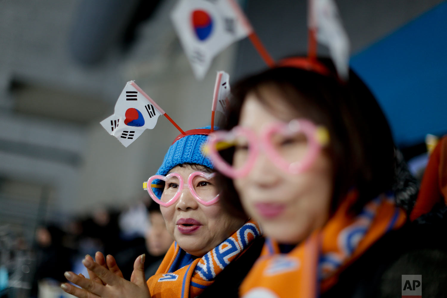 A spectator wearing a South Korean flag watches the mixed doubles semi-final curling match between Russian athletes and Switzerland at the 2018 Winter Olympics in Gangneung, South Korea, Monday, Feb. 12, 2018. (AP Photo/Natacha Pisarenko)