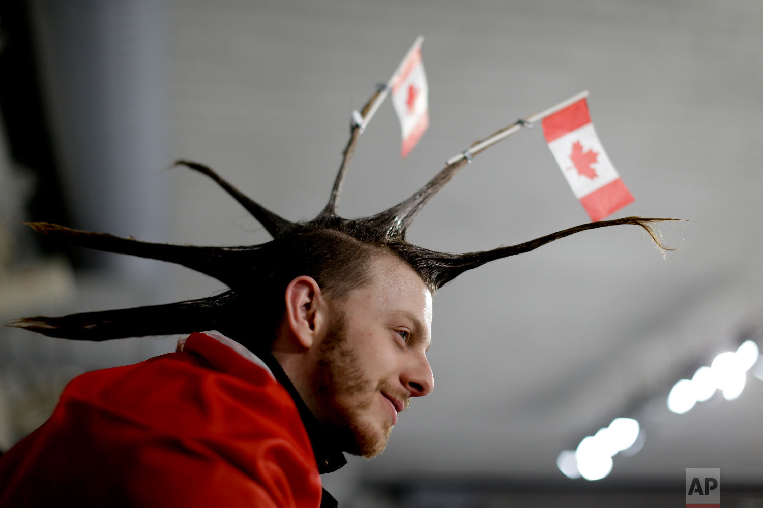 A spectator wearing the Canada flag on his hair watches the mixed doubles semi-final curling match between Russian athletes and Switzerland at the 2018 Winter Olympics in Gangneung, South Korea, Monday, Feb. 12, 2018. (AP Photo/Natacha Pisarenko)