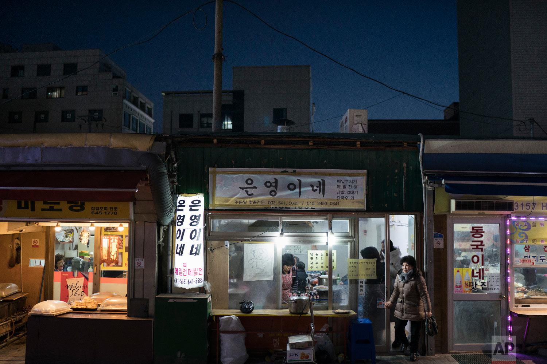 A woman leaves a restaurant in Gangneung, South Korea, Monday, Feb. 12, 2018. (AP Photo/Felipe Dana)