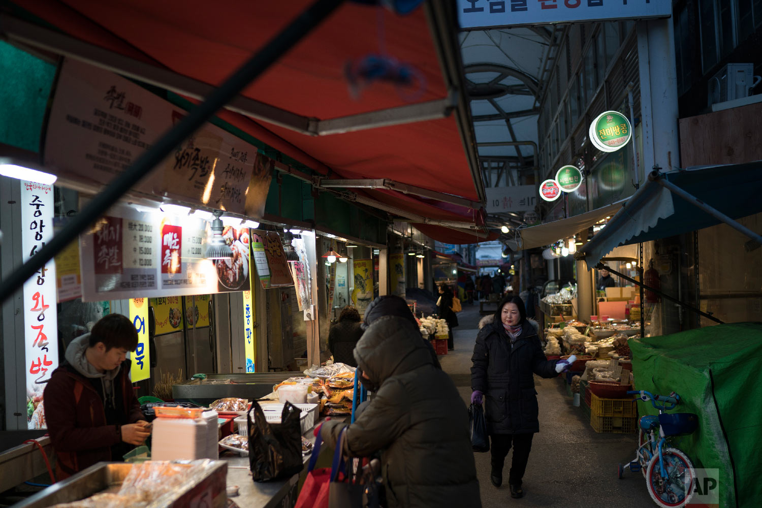 People shop at the traditional market in Gangneung, South Korea, Tuesday, Feb. 13, 2018. (AP Photo/Felipe Dana)