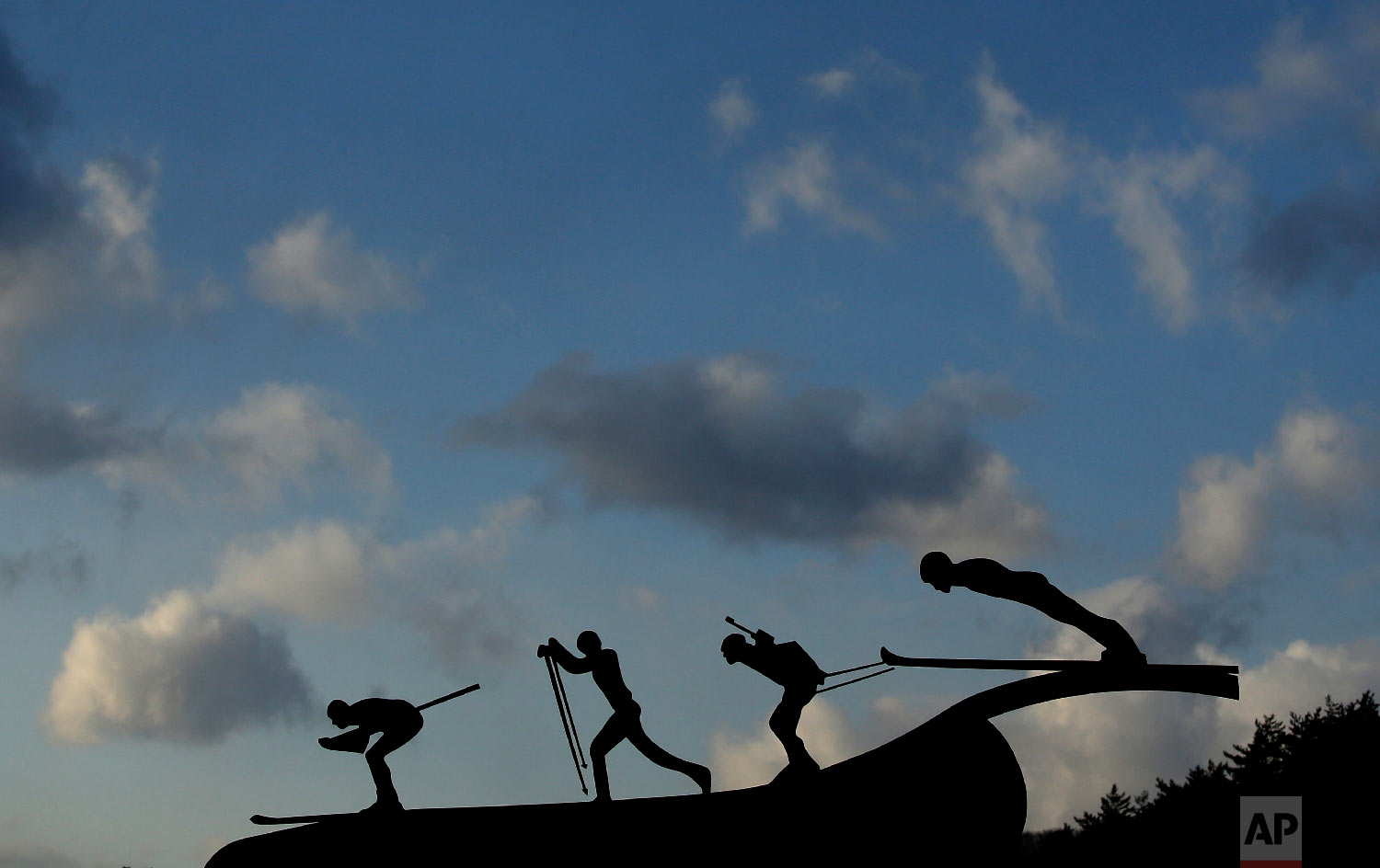 A sculpture of skiers outside the Alpensia Ski Jumping Center is silhouetted against the sky at sunset at the 2018 Winter Olympics in Pyeongchang, South Korea, Friday, Feb. 2, 2018. (AP Photo/Charlie Riedel)