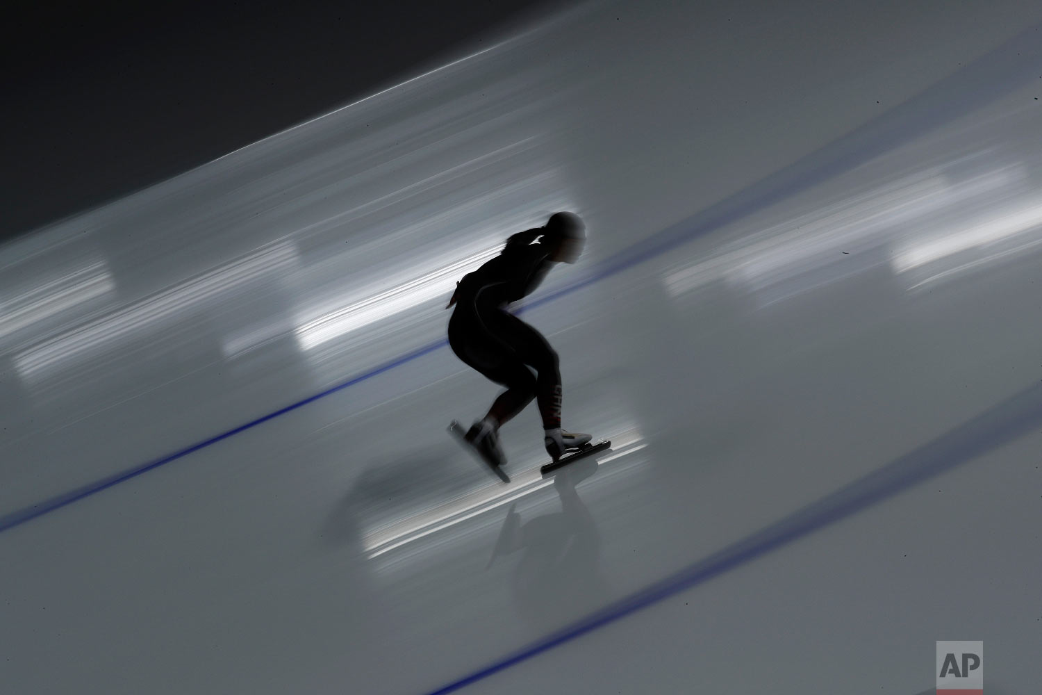 A female athlete from China is silhouetted against the reflection of a spotlight on the ice during the women's 500 meters speedskating practice session at the Gangneung Oval at the 2018 Winter Olympics in Gangneung, South Korea, Saturday, Feb. 17, 2018. (AP Photo/John Locher)
