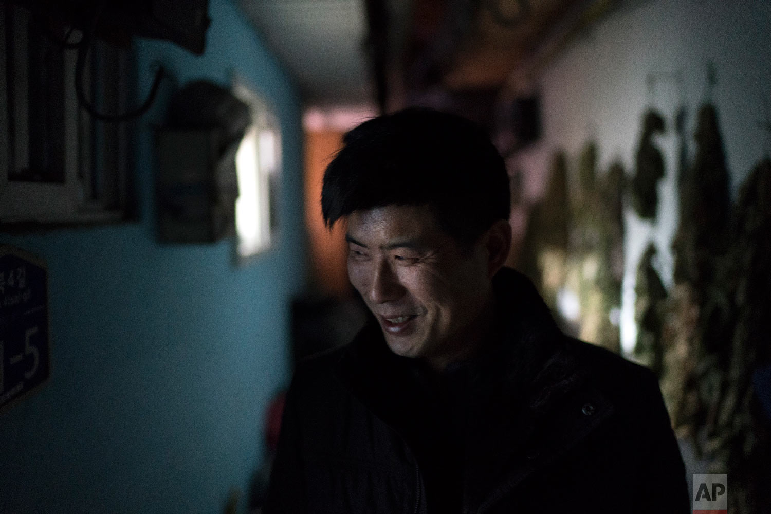 Lee Sang-kyu, 52, stands in an alley outside his mother's house in the town of Sabuk, Jeongseon county, South Korea, Thursday, Feb. 15, 2018. (AP Photo/Felipe Dana)
