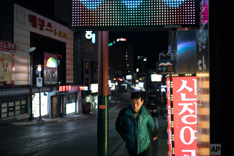 A man walk past neon-lit signs in the town of Sabuk, Jeongseon county, South Korea, Thursday, Feb. 15, 2018. (AP Photo/Felipe Dana)