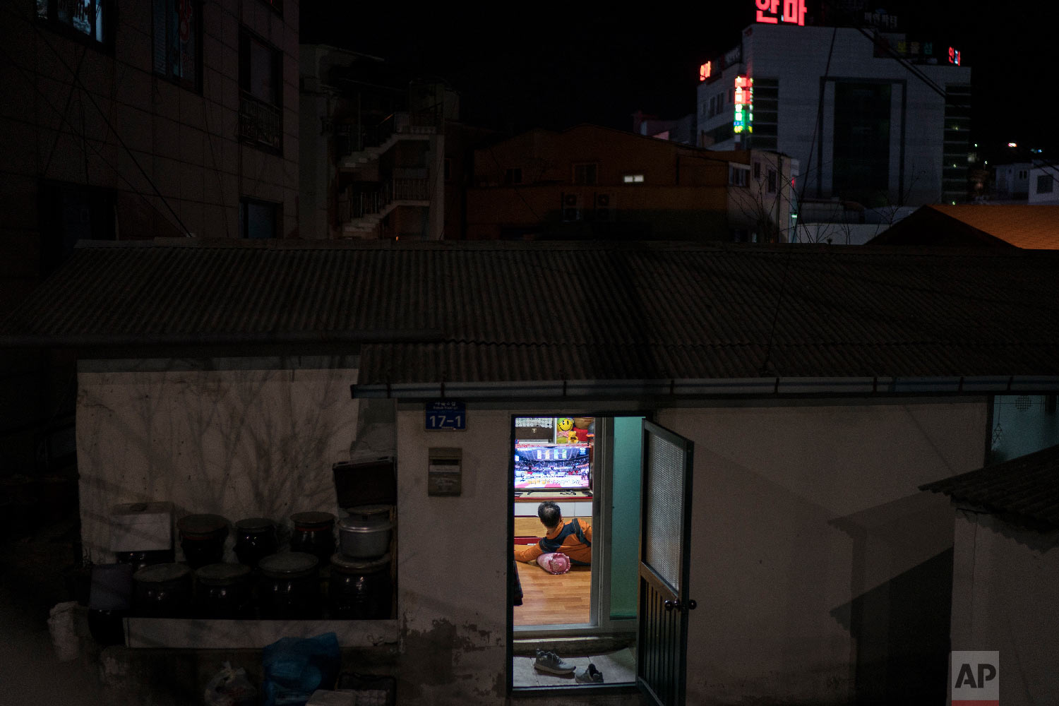 A man watches the Winter Olympics transmission on a television inside his house in the town of Sabuk, Jeongseon county, South Korea, Thursday, Feb. 15, 2018. (AP Photo/Felipe Dana)