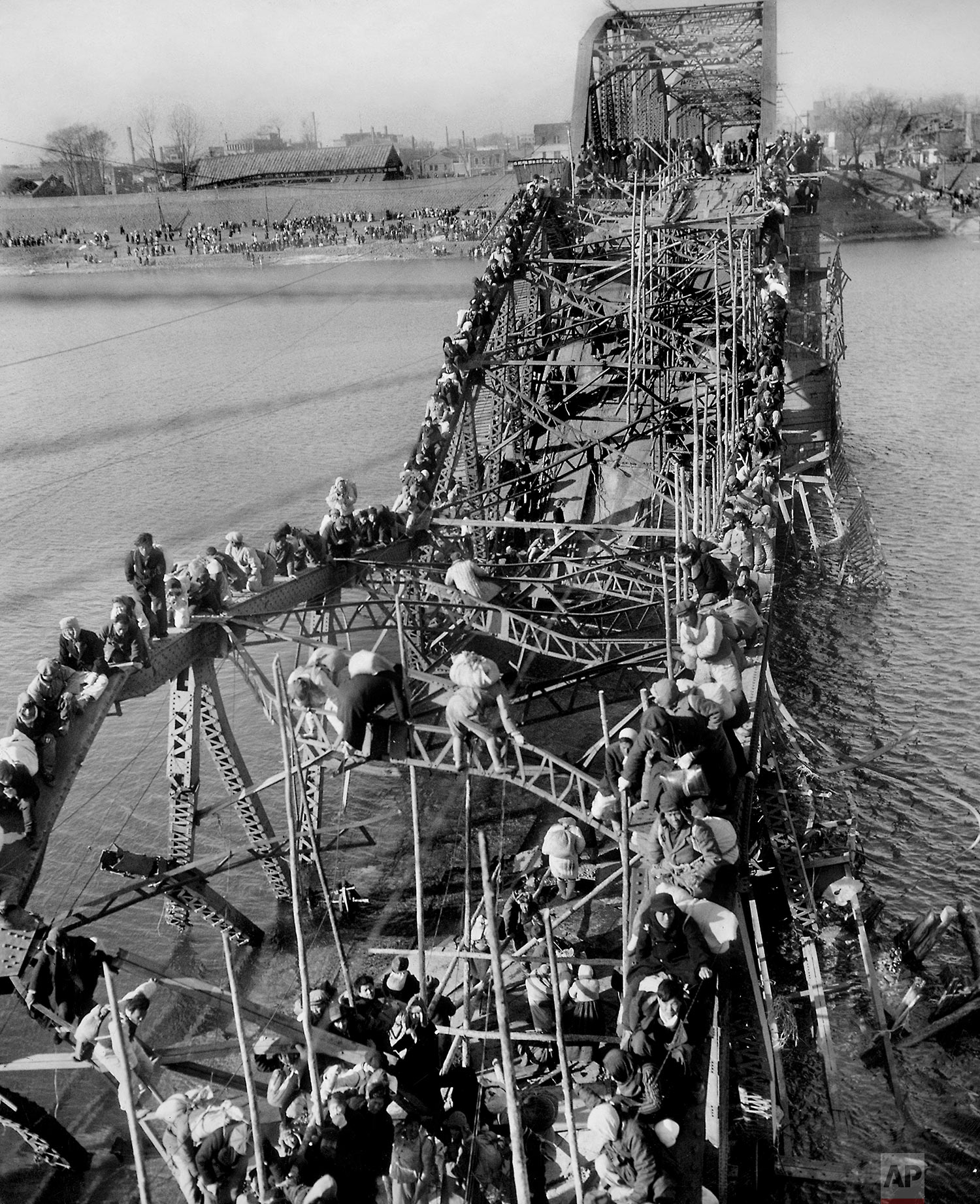 Residents from Pyongyang, North Korea, and refugees from other areas crawl perilously over shattered girders of the city's bridge on Dec. 4, 1950, as they flee south across the Taedong River to escape the advance of Chinese Communist troops. (AP Photo/Max Desfor)