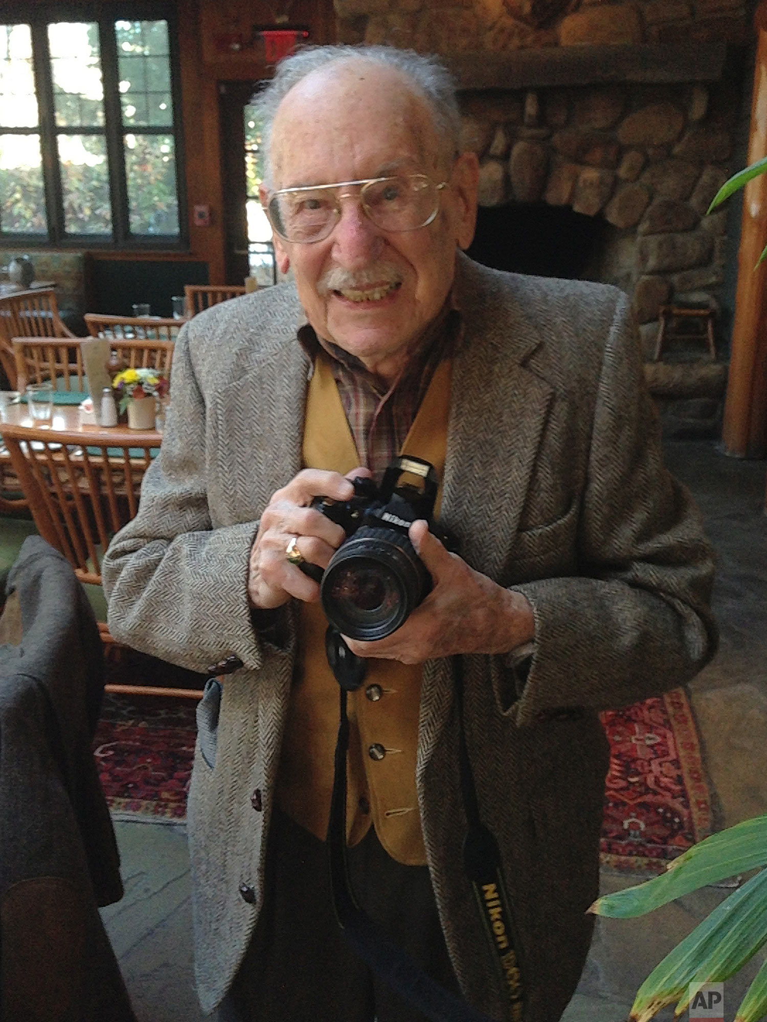 Max Desfor pauses for a photo on Nov. 16, 2012, in Rockville, Md., at his 99th birthday party. Desfor, a former Associated Press photographer who won a Pulitzer Prize for his coverage of the Korean War died Monday, Feb. 19, 2018. He was 104.  (AP Photo/Jon Elswick)