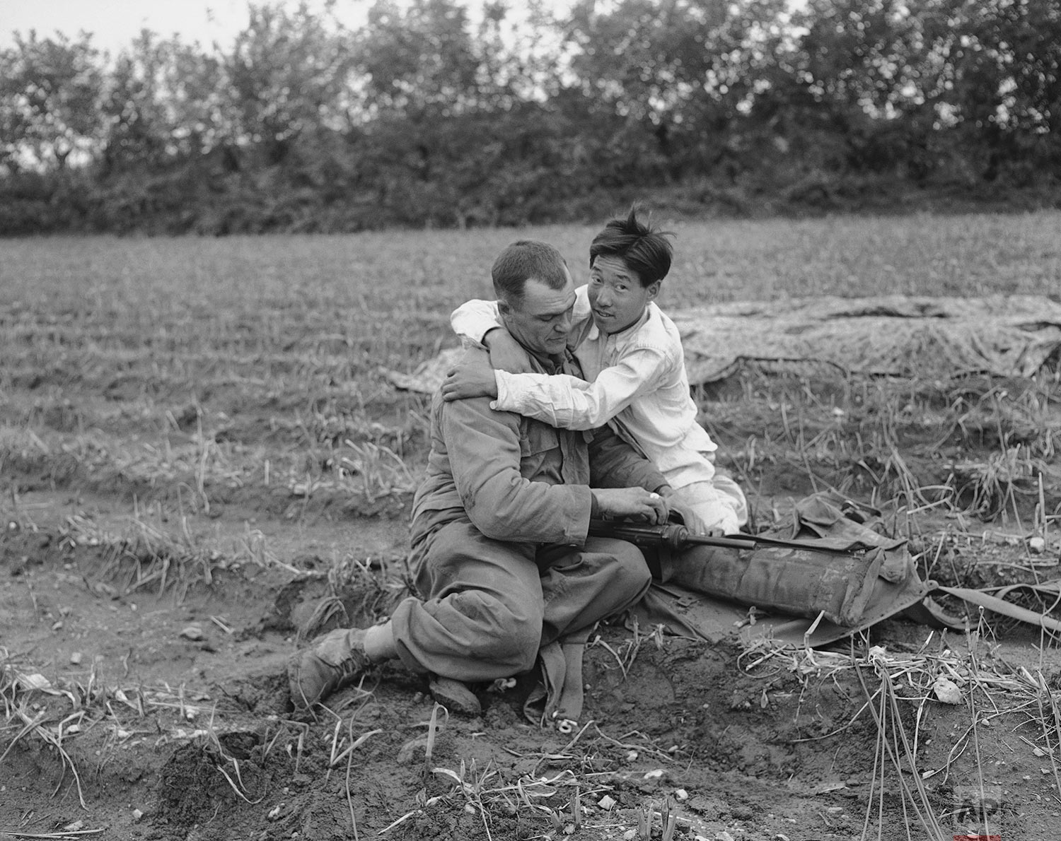 Paratrooper embraced by native after he hit ground in Sunchon, North Korea on Oct. 20, 1950. (AP Photo/Max Desfor)