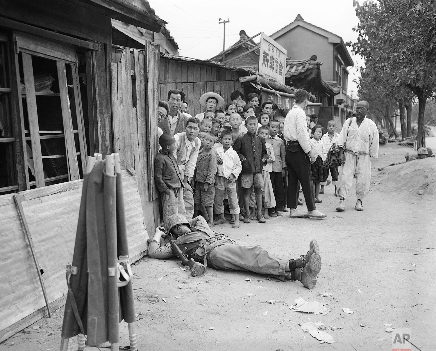 Fatigue, not an enemy bullet, stopped this American marine who catches 40 winks on a Seoul Street unperturbed by his audience of young and old residents in Seoul, Sept. 28, 1950. (AP Photo/Max Desfor)