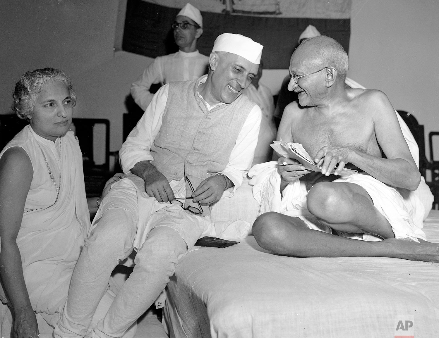 In this July 6, 1946, photo, a bespectacled Mohandas Gandhi, the Mahatma, who eventually led India to its independence, laughs with the man who was to be the nation's first prime minister, Jawaharlal Nehru, at the All-India Congress committee meeting in Bombay, India. Atleft is Madam Vijaya Lakshmi Pandit.  (AP Photo/Max Desfor)