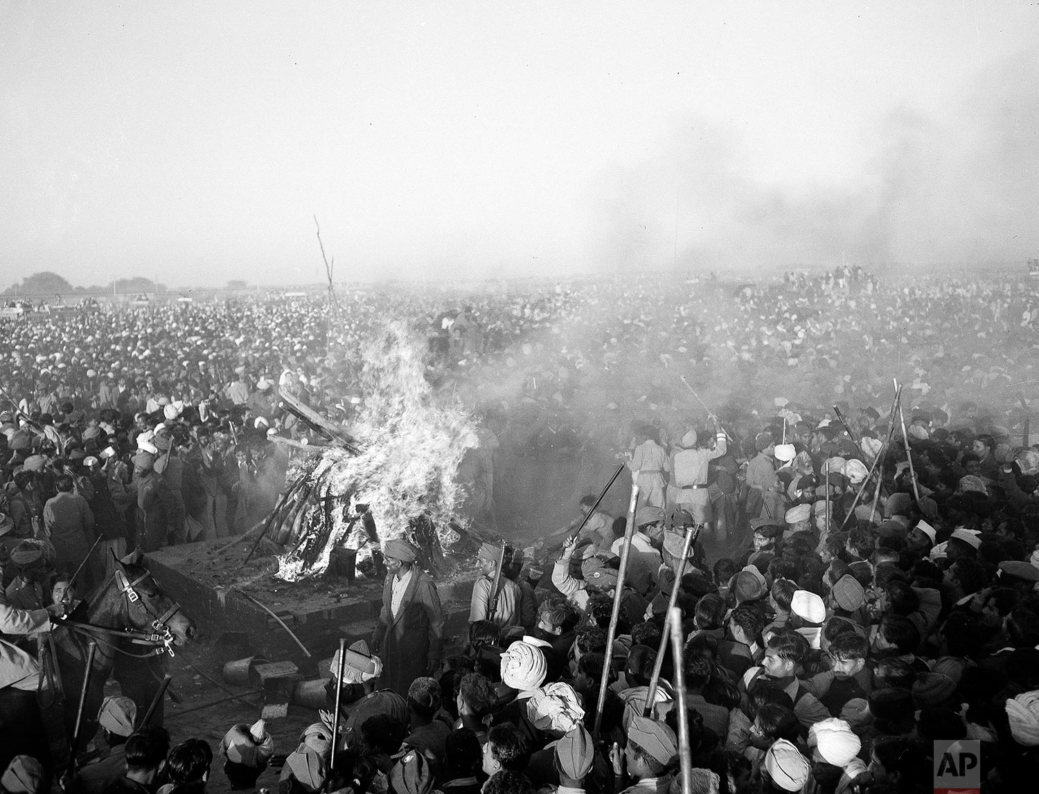 Police, the military and volunteer guards attempt to beat back the crowds as it surges forward towards the funeral pyre of Mohandas K. Gandhi, assassinated Indian spiritual leader, in New Delhi, Jan. 31, 1948. (AP Photo/Max Desfor)