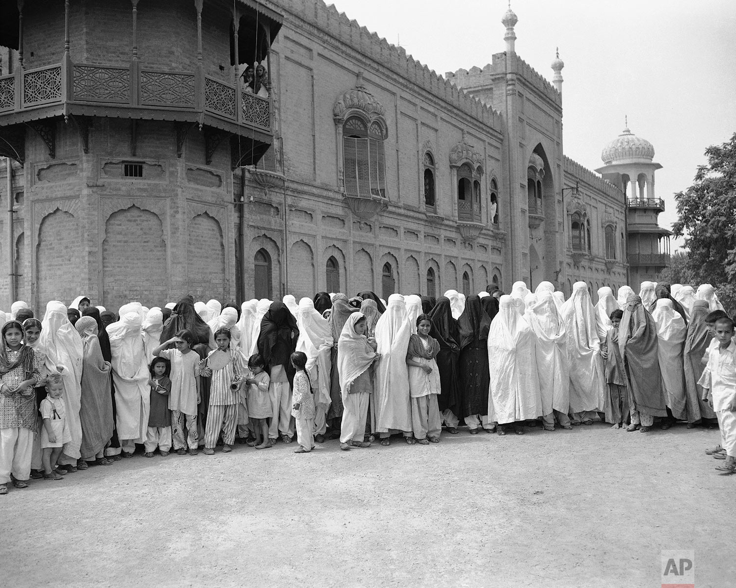 Muslim women, wearing burkahs to keep strict purdah, await their turn to proceed to the polling rooms at the Griffis High School grounds, July 9, 1947 in Peshawar, where they will take part in the referendum voting. (AP Photo/Max Desfor)