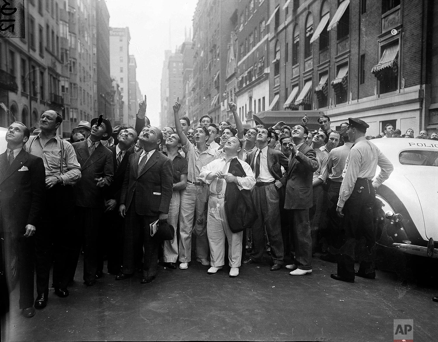 A curious crowd of thousands of onlookers nervously watch John Ward, as he perched himself on a ledge on the 17th floor of the Gothan Hotel on Fifth Avenue in New York, threatening to jump, July 26, 1938. Several times spectators scurried backward as it appeared ward would leap from his precarious perch. (AP Photo/Max Desfor)